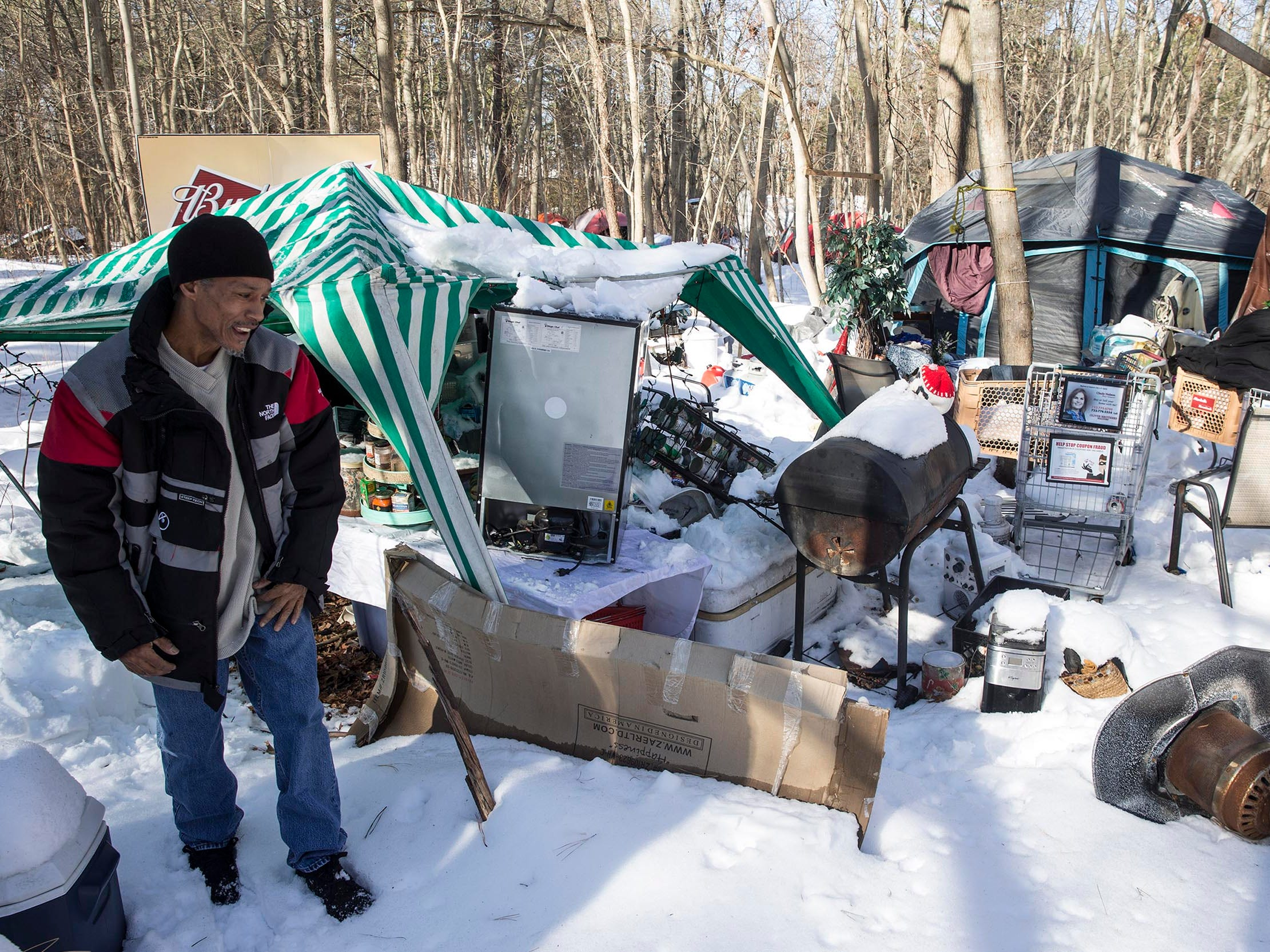 Carlos Santiago attempts to clean up the camp that took a beating from snow and cold weather recently.  About one dozen homeless people who live in a small encampment in the woods have been staying at the Crystal Inn since severe cold weather and snow hit the area. Donations collected made the hotel stay possible.   Neptune, NJ on Wednesday, January 10, 2018