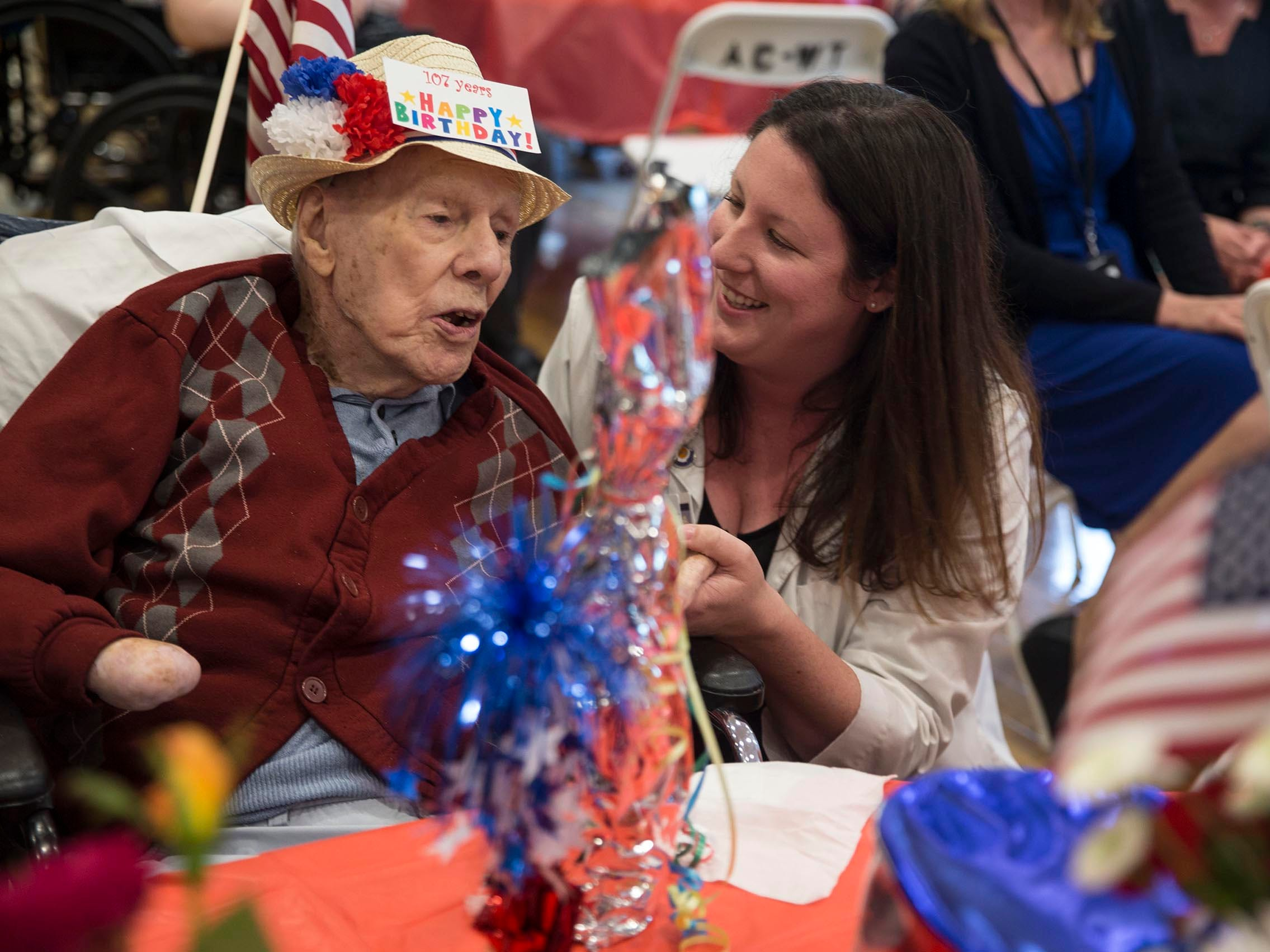 World War II veteran and Flying Tiger Bill Laun of Manchester, is honored with a party for turning 107 years old. Michelle Engroff of VNA Group presents Laun with a bottle of German wine for his birthday in Manchester, NJ on June 8, 2018