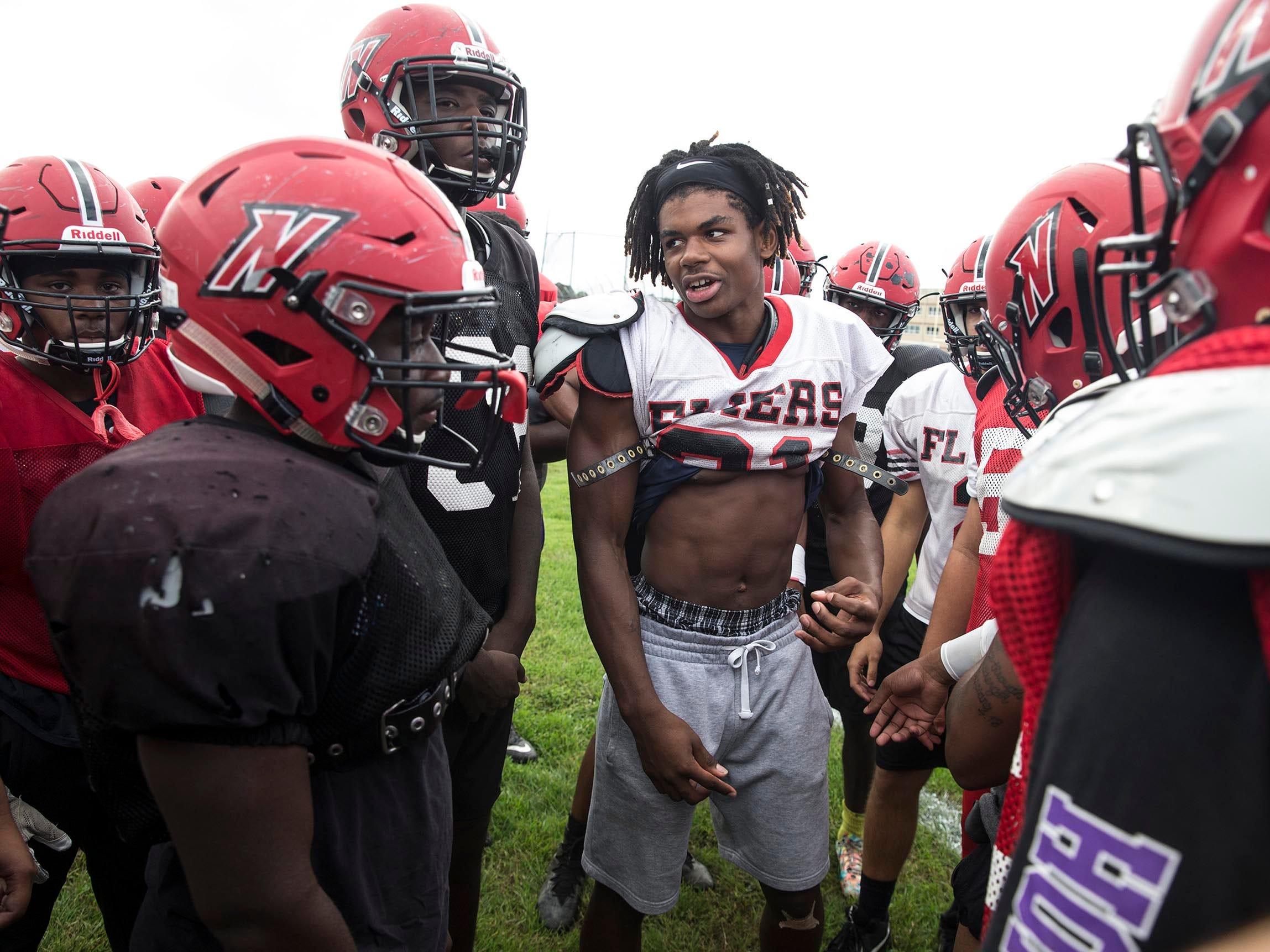 The Neptune Township High School football team has got off to a good start with the help of head coach Tarig Holman. Najiere Hutchinson, center in white shirt, gets his team fired up for practice.