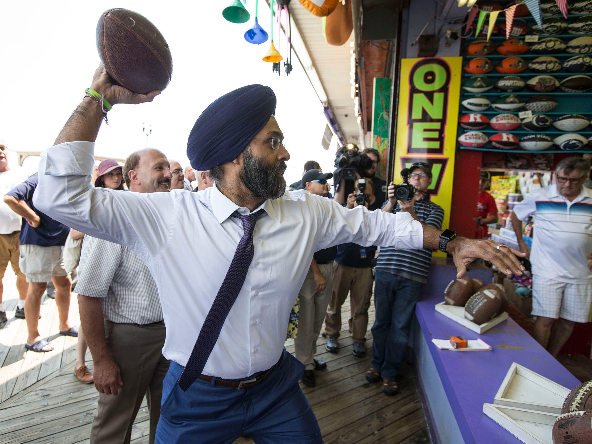 "Grewal tries his luck at a football toss boardwalk game. New Jersey Attorney General Gurbir S. Grewal and Acting Director, Division of Consumer Affairs Paul R. Rodriguez (speaking) announce ""Safe Summer"" boardwalk inspections to check boardwalk games for fairness to play."