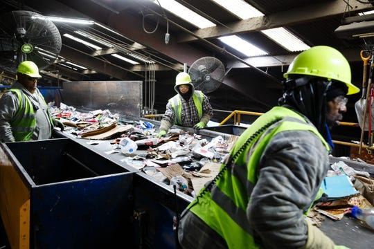 Workers at the Mid America Recycling facility do an initial scan by hand pulling out any large items that would stop production or damage the machines on Nov. 29, 2018, in Des Moines