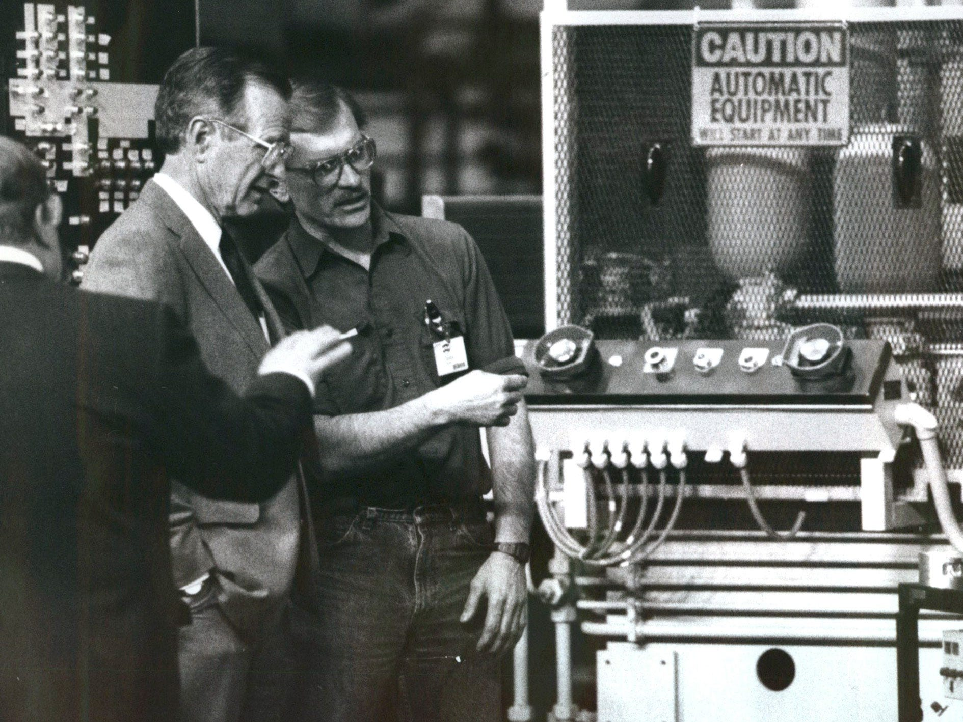 Machine welder Chuck Kasler explains his work area to President George Bush at a tooling plant in Fraser in April 1992.