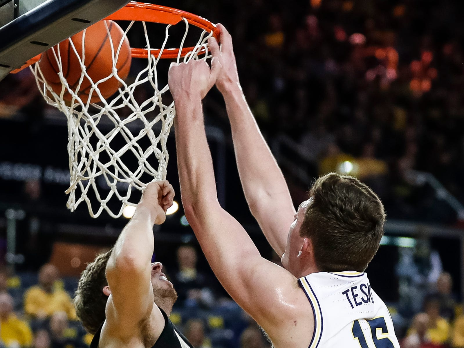 Michigan center Jon Teske (15)  dunks against Purdue guard Ryan Cline (14) during the first half at Crisler Center on Saturday, Dec. 1, 2018.