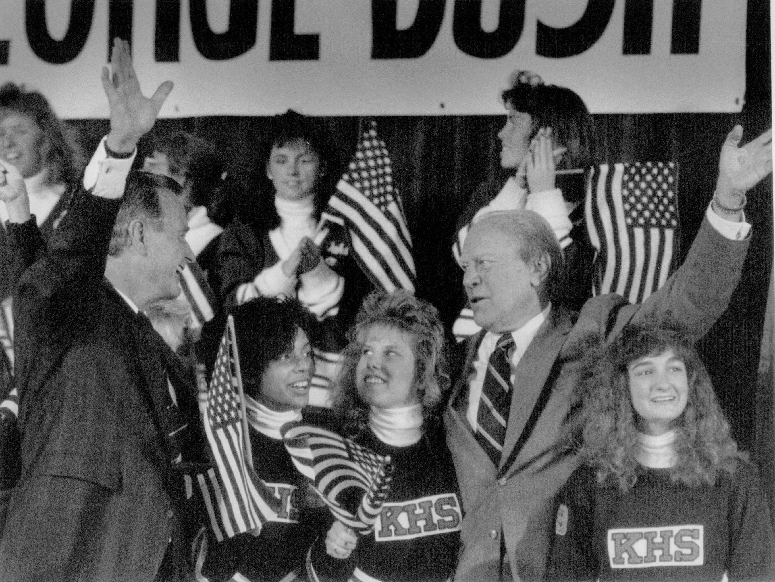 Royal Oak's Kimball HS cheerleaders watch as President Gerald Ford and Vice President George Bush wave to the crowd at Royal Oak's Kimball High School in October 1988.