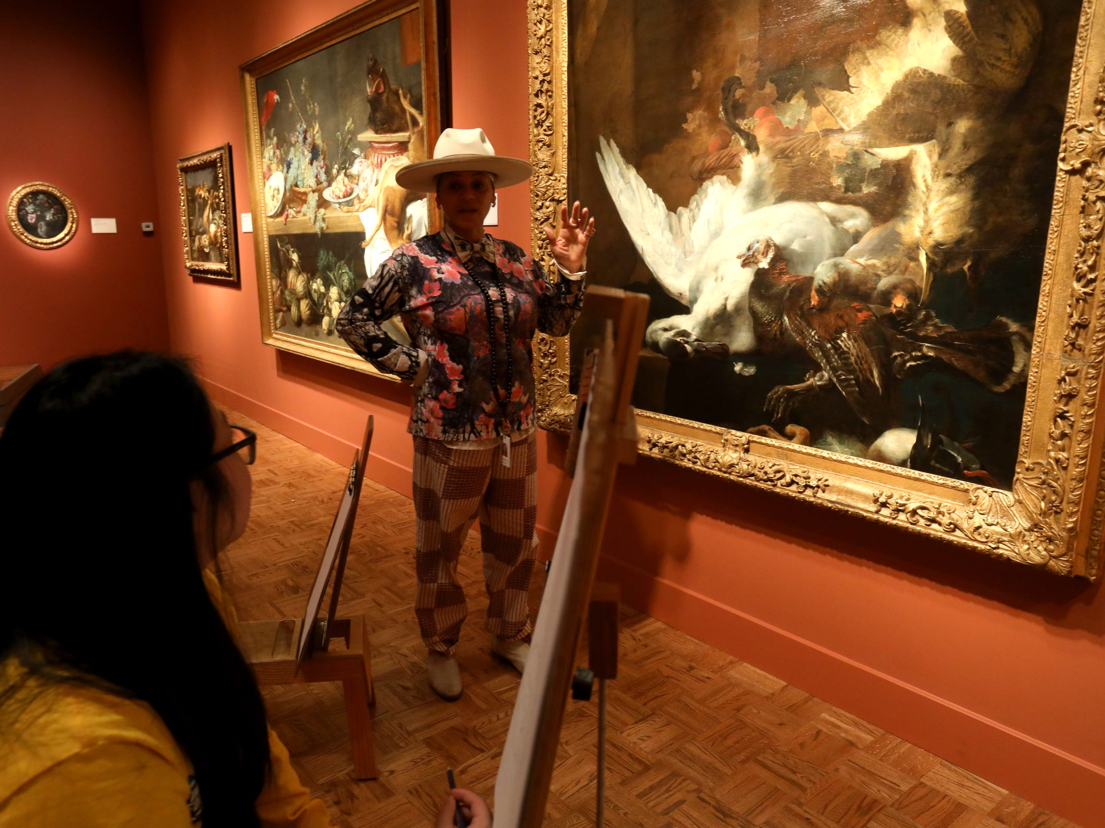 "From left, Chelsea Young, 22 of Detroit listens as Sabrina Nelson, of Detroit talks about what to see when drawing ""Still Life with a Dead Swan"" by Jan Baptist Weenix. Nelson is one of the Learning and Interpretation employees at the Detroit Institute of Arts and was leading the Drawing in the Galleries program on Saturday, December 1, 2018 during Noel Night at the Detroit Institute of Arts in Detroit."