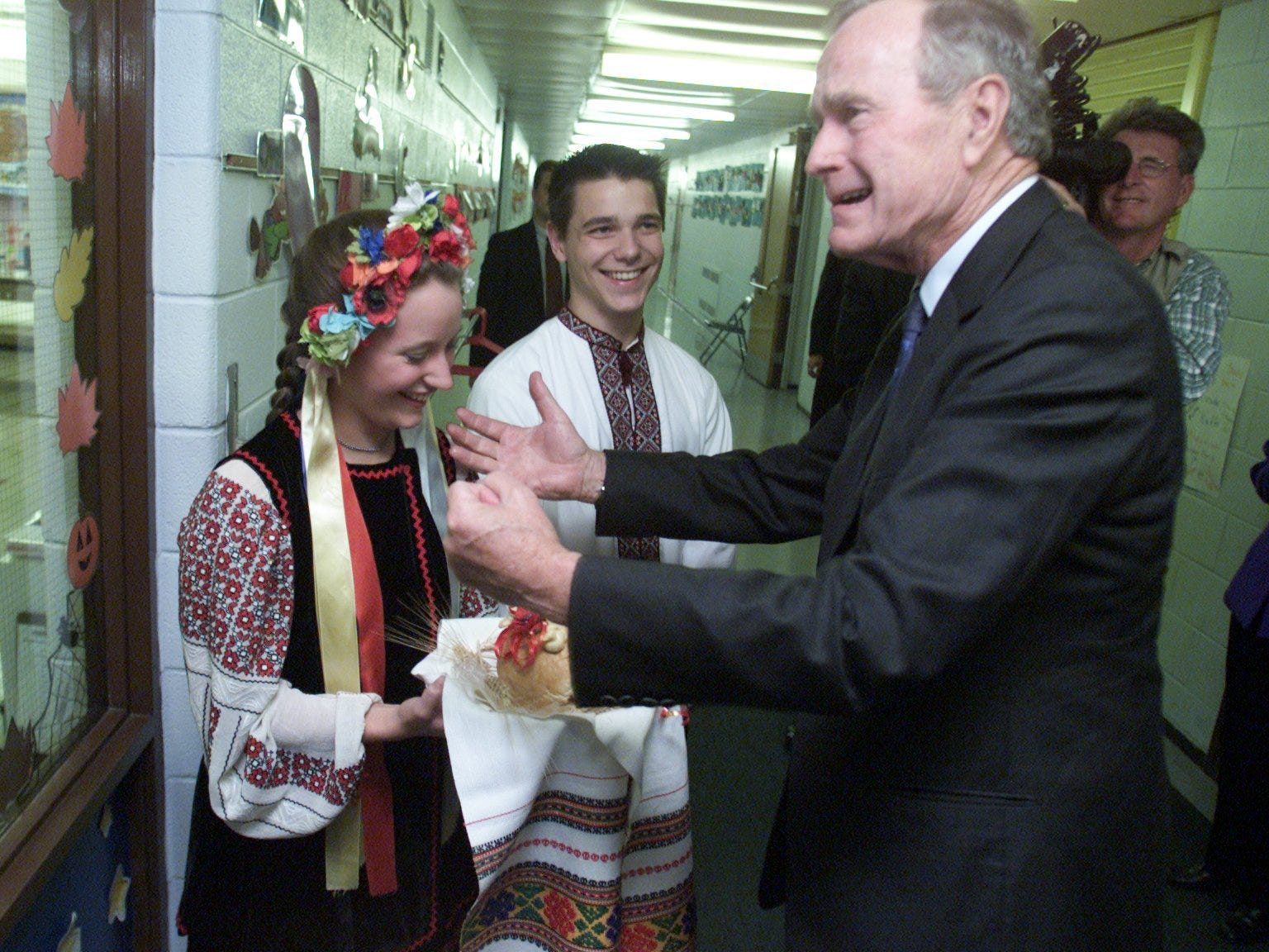Former President George Bush  is greeted by Immaculate Conception Ukrainina Catholic School seniors Natalie Tobianski and Mark Tarnavsky in October 2000.   Tobianski, dressed in traditional Ukraine clothing from the region of Poltava and offers Bush bread and salt said to represent life and prosperity. Bush is visiting the Warren school in hopes of  drumming up support for his son George W. Bush who is running for the Presidency.