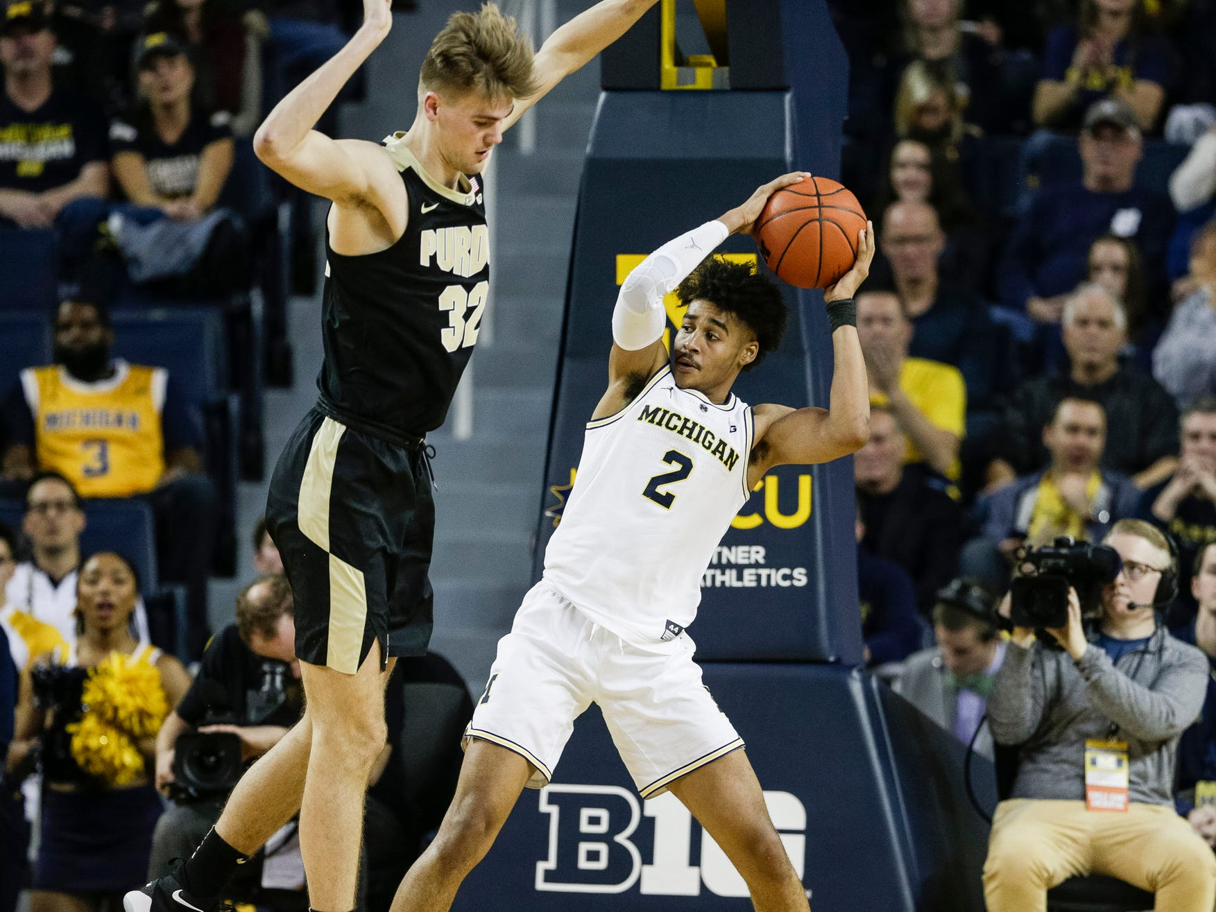 Michigan guard Jordan Poole (2) tries to pass the ball after getting a defensive rebound against Purdue center Matt Haarms (32) during the first half at Crisler Center on Saturday, Dec. 1, 2018.