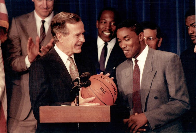 Isiah Thomas presents President George Bush with an a team-autographed basketball during their visit to Washington in June 1989. Bill Laimbeer (far left, back) and Vinnie Johnson (center) look on.