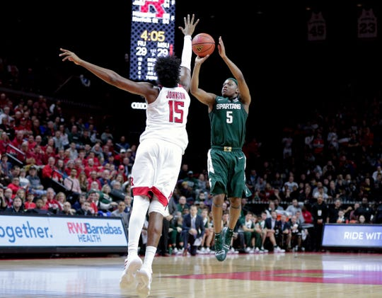 Michigan State guard Cassius Winston shoots as Rutgers center Myles Johnson defends during the first half at Rutgers Athletic Center, Nov. 30, 2018.