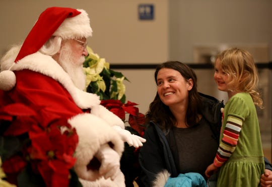 As mom Lindsay Pielack, 42 of Detroit looks on, Santa Claus talks with her daughter June Pielack, 4, during a meet and greet at the Detroit Institute of Arts during Noel Night on Saturday, December 1, 2018.