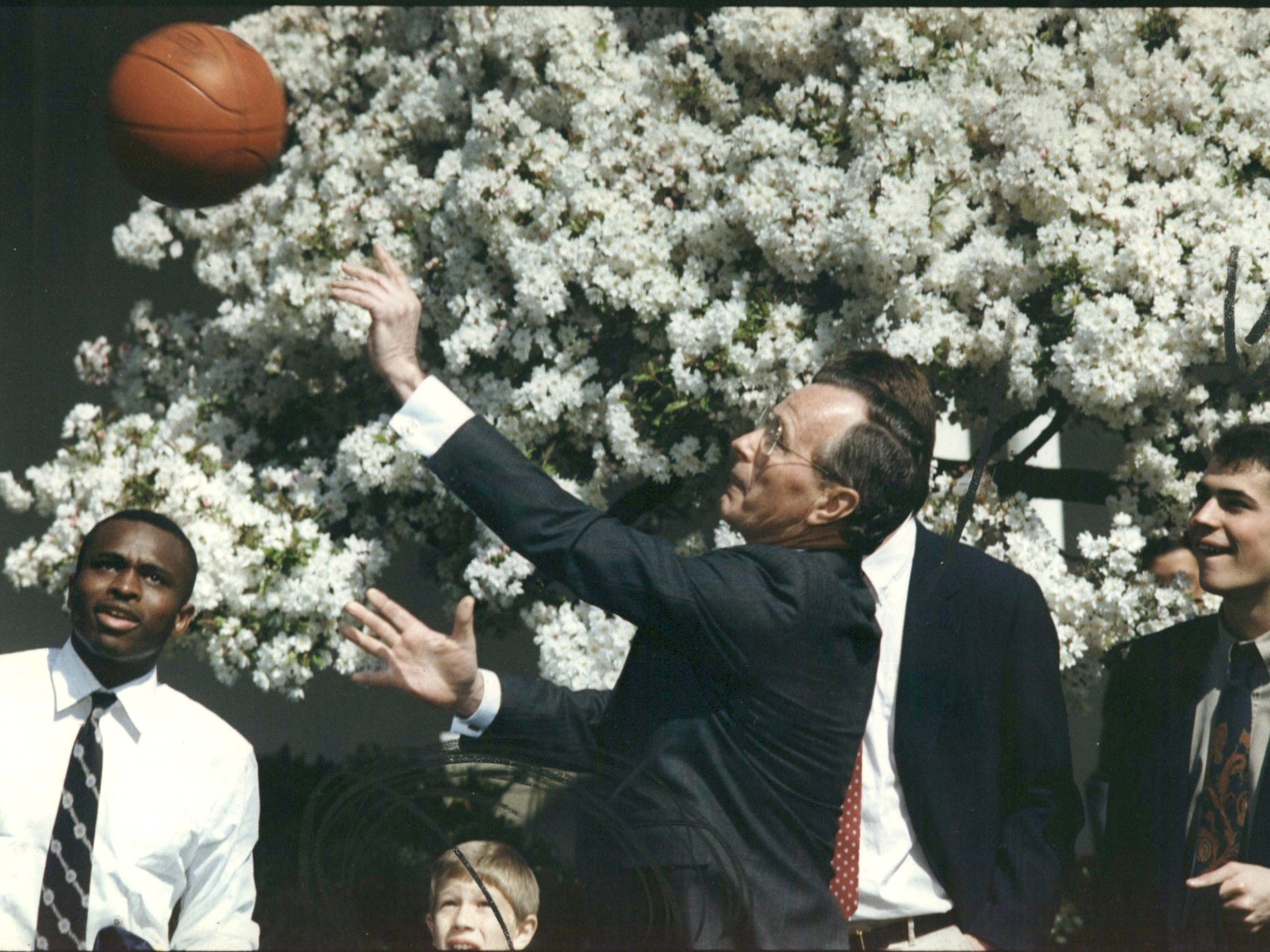President George Bush shoots a free throw in April 1989 at a portable basket in the White House Rose Garden as University of Michigan players watch. The NCAA champion Wolverines were the guests of Bush, who sank the free throw, though the ball did bounce around the rim. From left are Rumeal Robinson, J.P. Oosterbaan and Rob Pelinka.