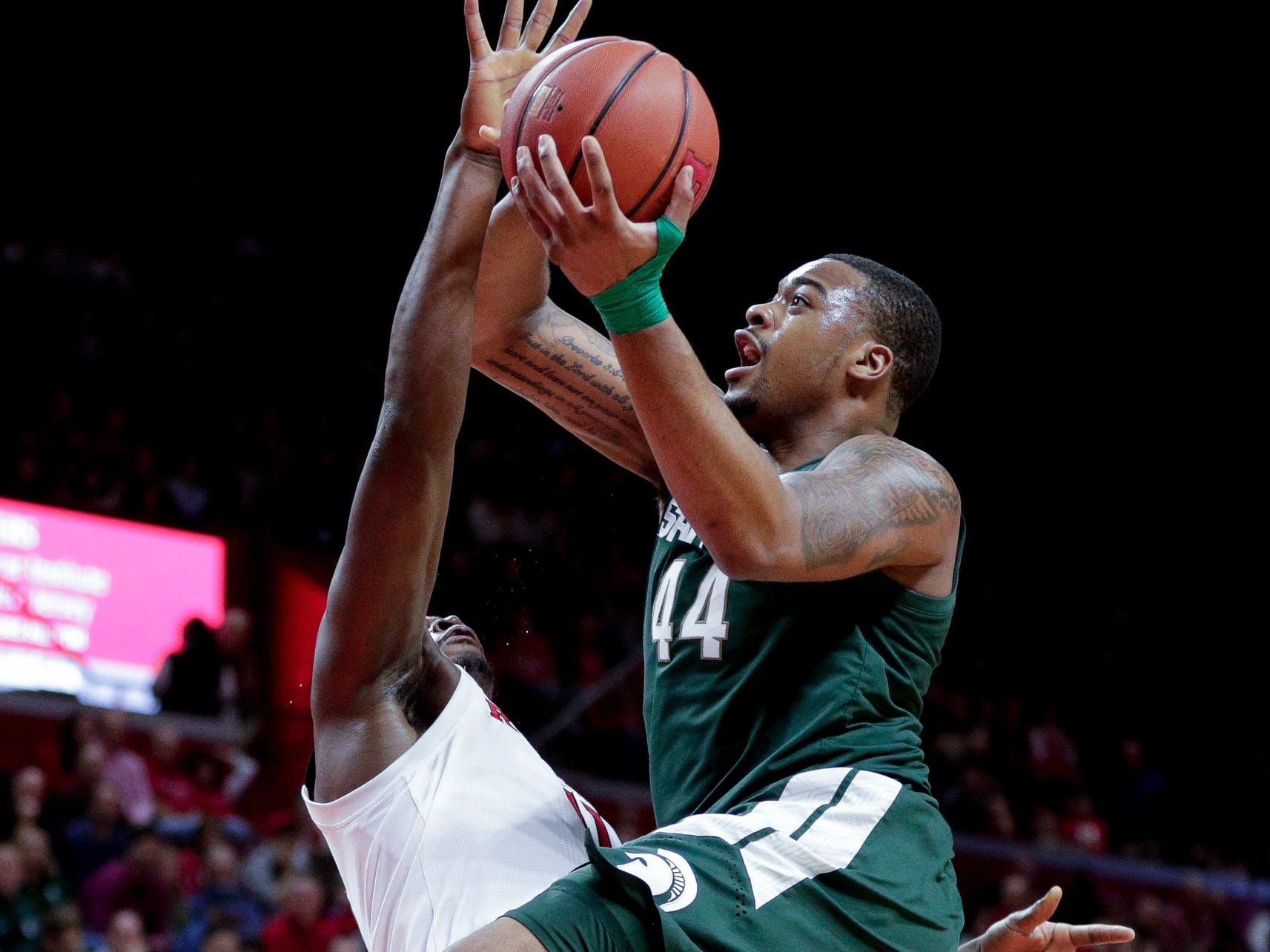Michigan State forward Nick Ward drives to the basket as Rutgers forward Mamadou Doucoure defends during the first half at Rutgers Athletic Center, Nov. 30, 2018.