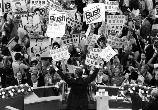 George H.W. Bush, center foreground, acknowledges the crowd before speaking to the Republican Convention delegates in Detroit on July 16, 1980.