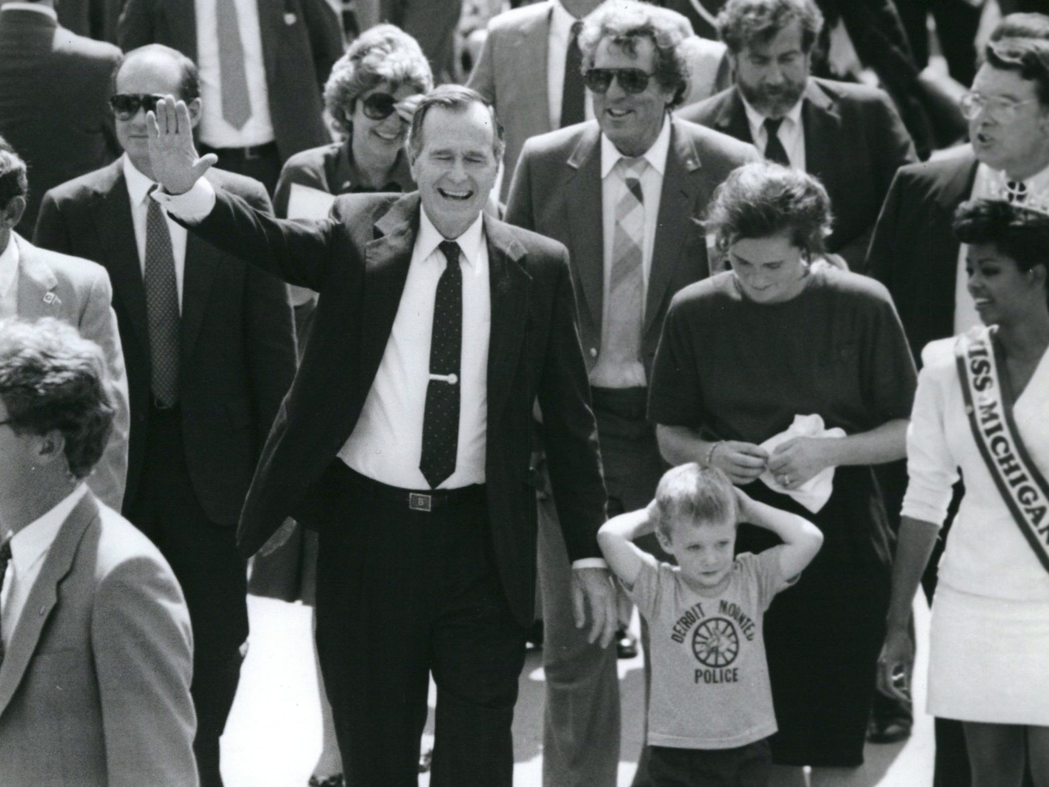 Republican presidential candidate George H.W. Bush walks at the Michigan State Fair with his grandson, Sam Leblonde, 3; his daughter, Dora Leblonde, and Anthonia Dotson, 20, and Miss Michigan State Fair in September 1988.