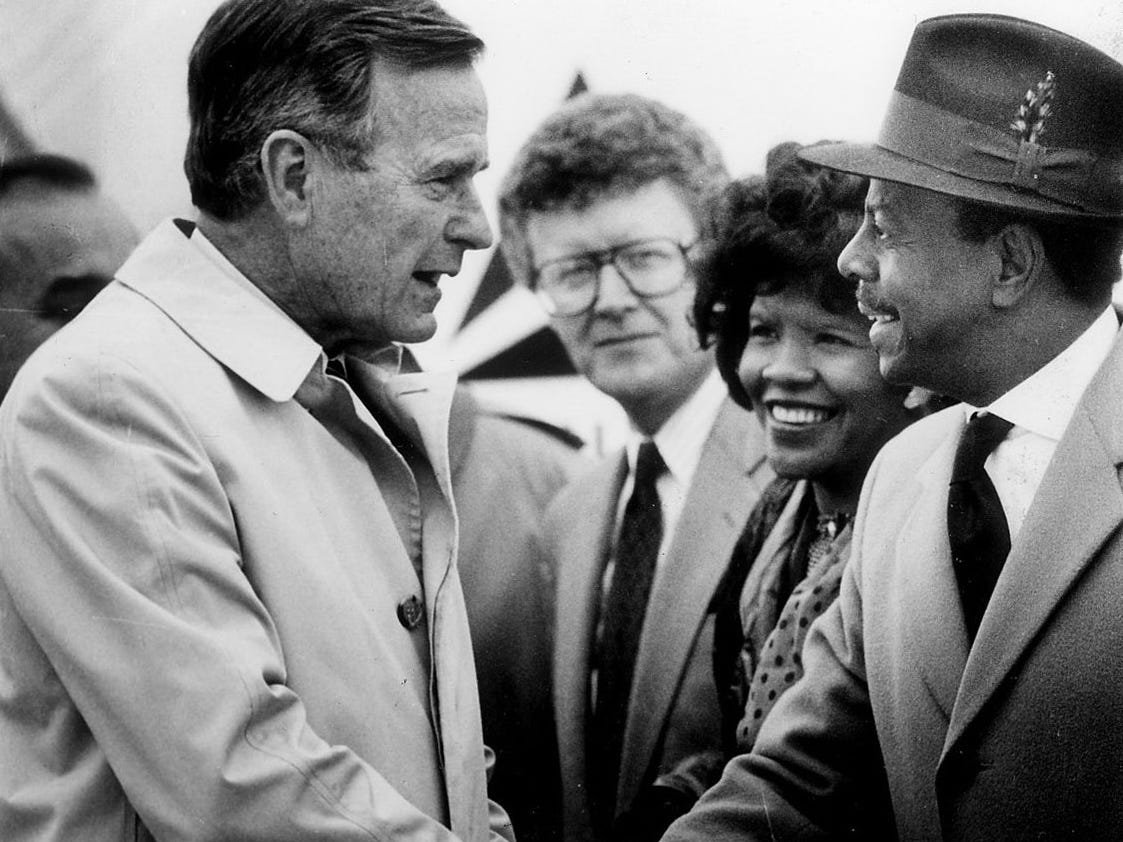President George Bush shakes hands with the Rev. Eddie Edwards of the Ravendale neighborhood during an abrupt, cold, noisy Metro Airport Ceremony in Romulus in April 1990.