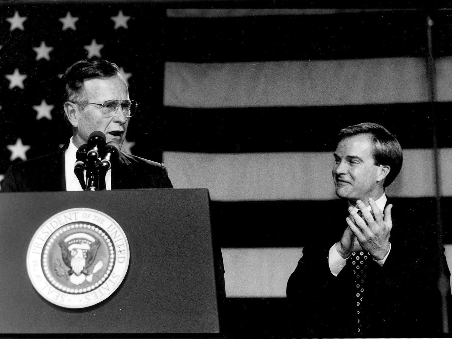 Bill Schuette, candidate for U.S. Senate, right, claps after introducing President George Bush during a Michigan visit in Septmber1990.