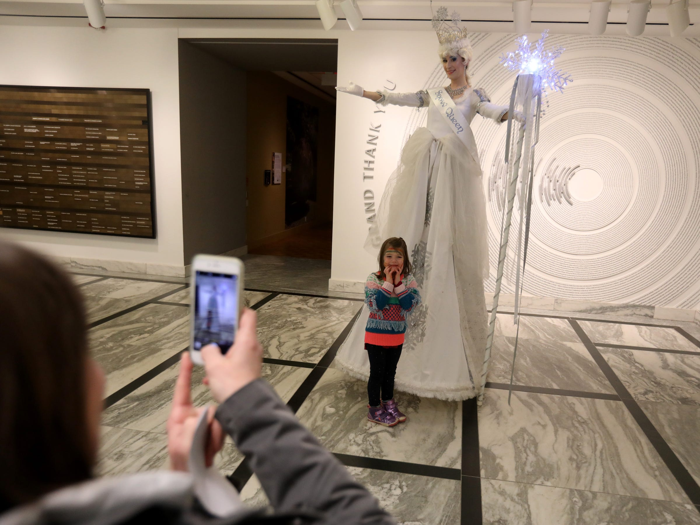 The Snow Queen poses with Hazel Mahoney, 4, of Detroit as her mother Mollie Mahoney takes a picture during Noel Night at the Detroit Institute of Arts in Detroit on Saturday, December 1, 2018.