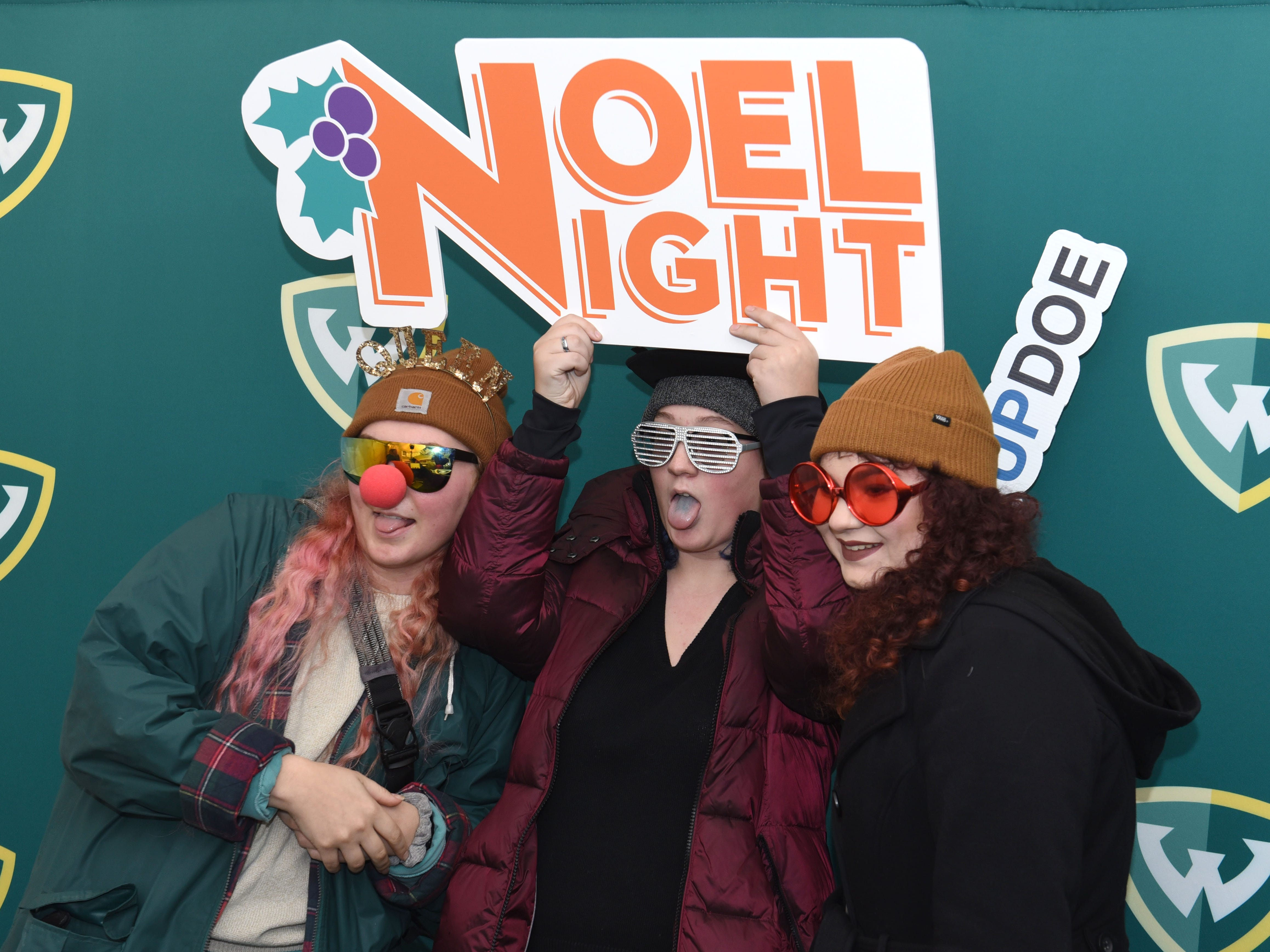 Kiera Molloy (from left) along with her sisters Riane Molloy and Meryn Molloy, of Farmington Hills, pose for a photograph at the Winter Art and Retail Market during Noel Night in Detroit on Saturday, December 1, 2018.