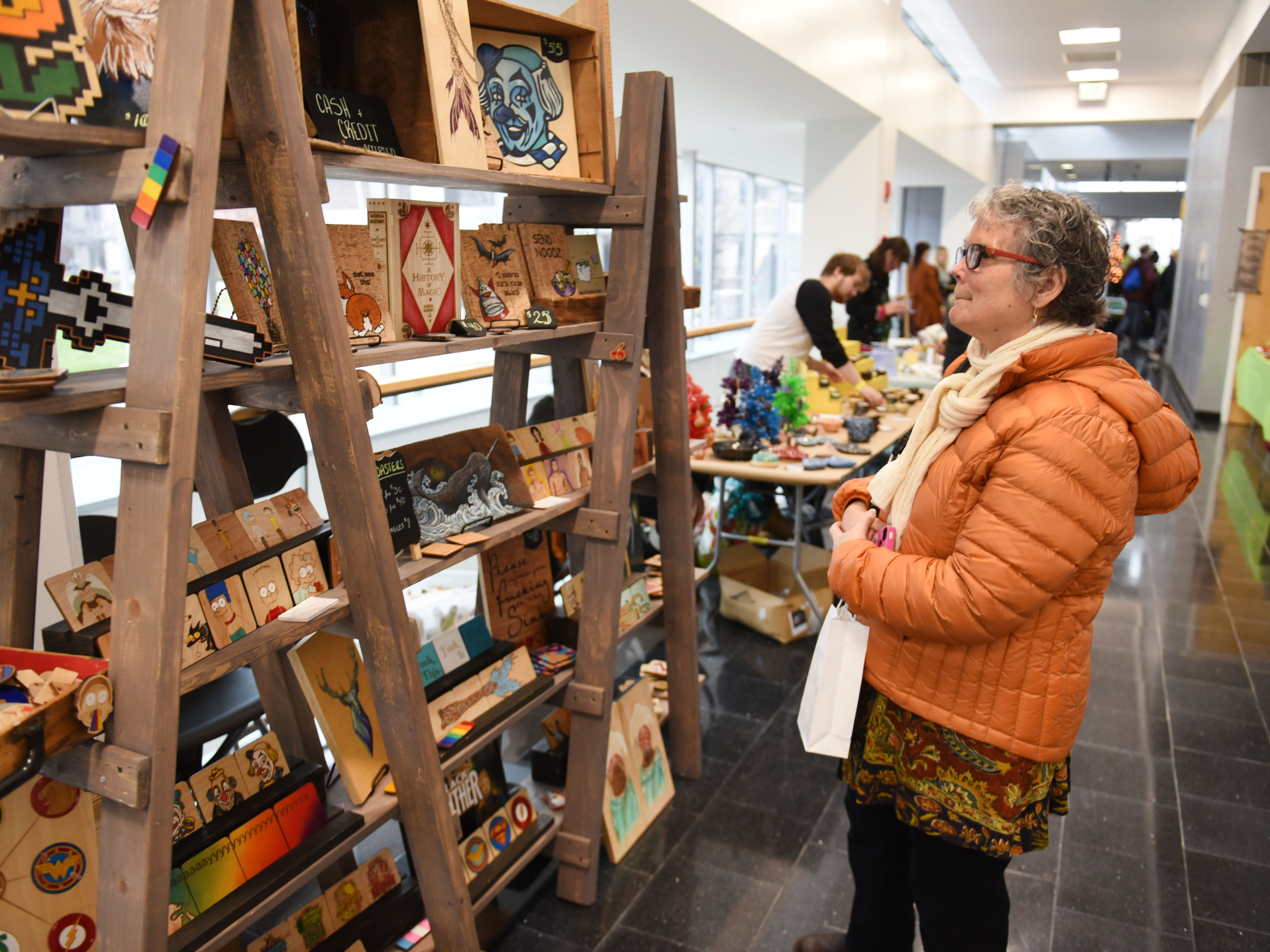 Judy Kales of Allen Park looks at the artwork of Jessica Rowland, of Pipperillo Studios, at the Annual Student Alumni Art Sale at the College of Creative Studies during Noel Night in Detroit on Saturday, December 1, 2018.