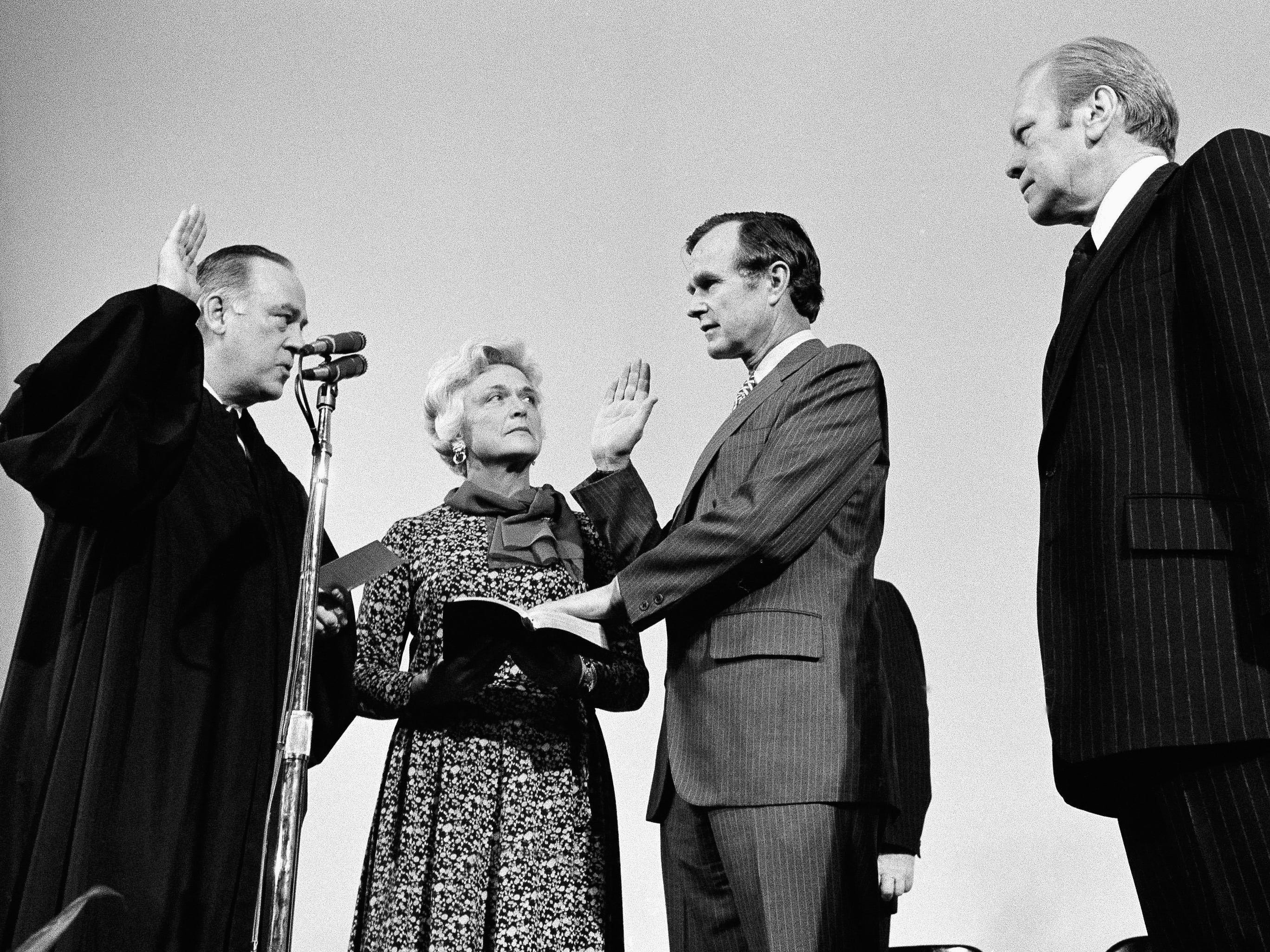 George H.W. Bush is sworn in as director of the Central Intelligence Agency by Supreme Court Associate Justice Potter Stewart, left, as Barbara Bush and President Gerald Ford, right, look on at CIA headquarters in Langley, Va.