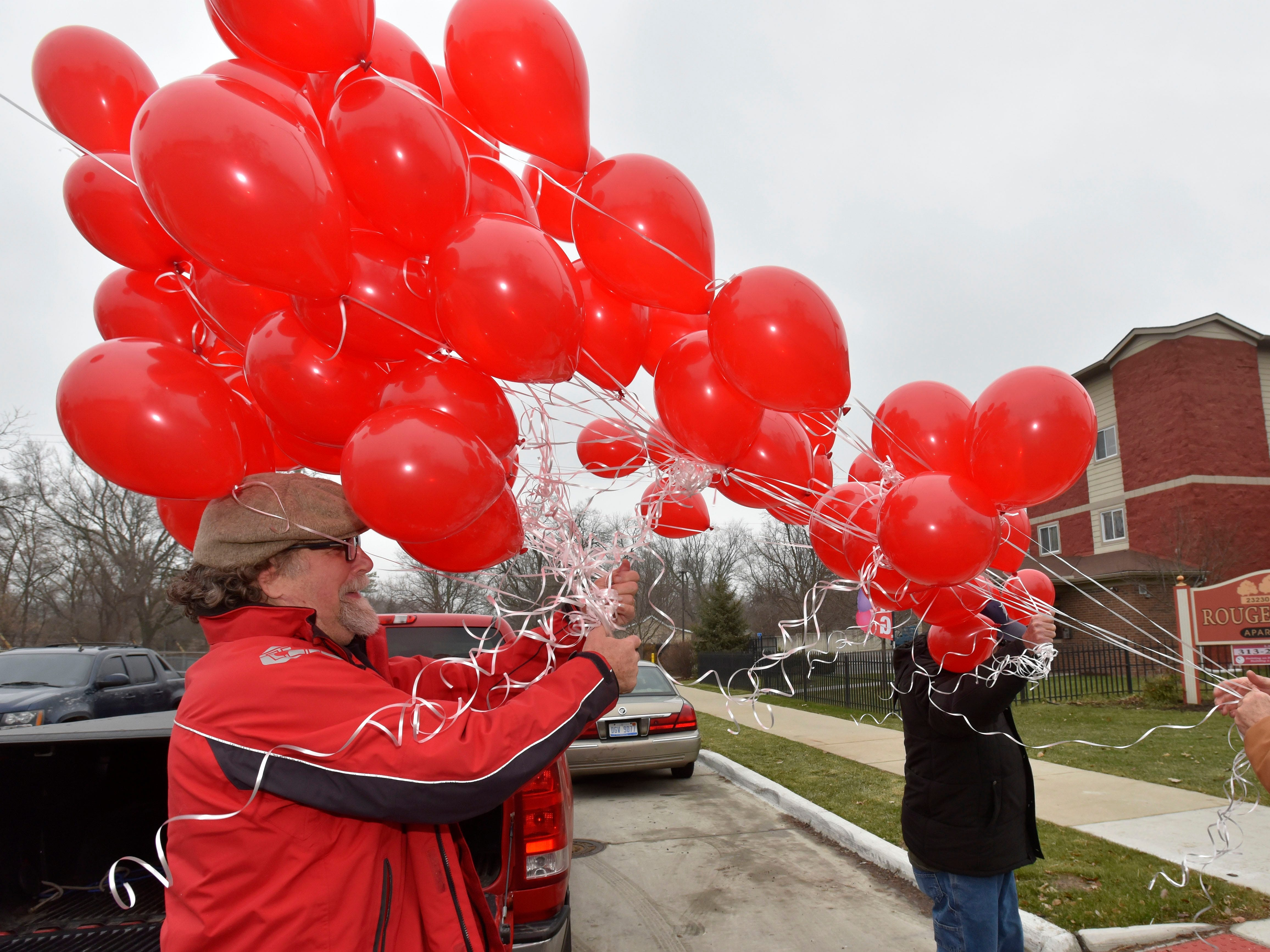 Detroit Eviction Defense member Richard Shackelford, left, of Detroit, delivers six dozen red balloons to protesters. KMG Prestige Management Company officials had posted red balloons on the residences of Brightmoor Homes late-rent payers.