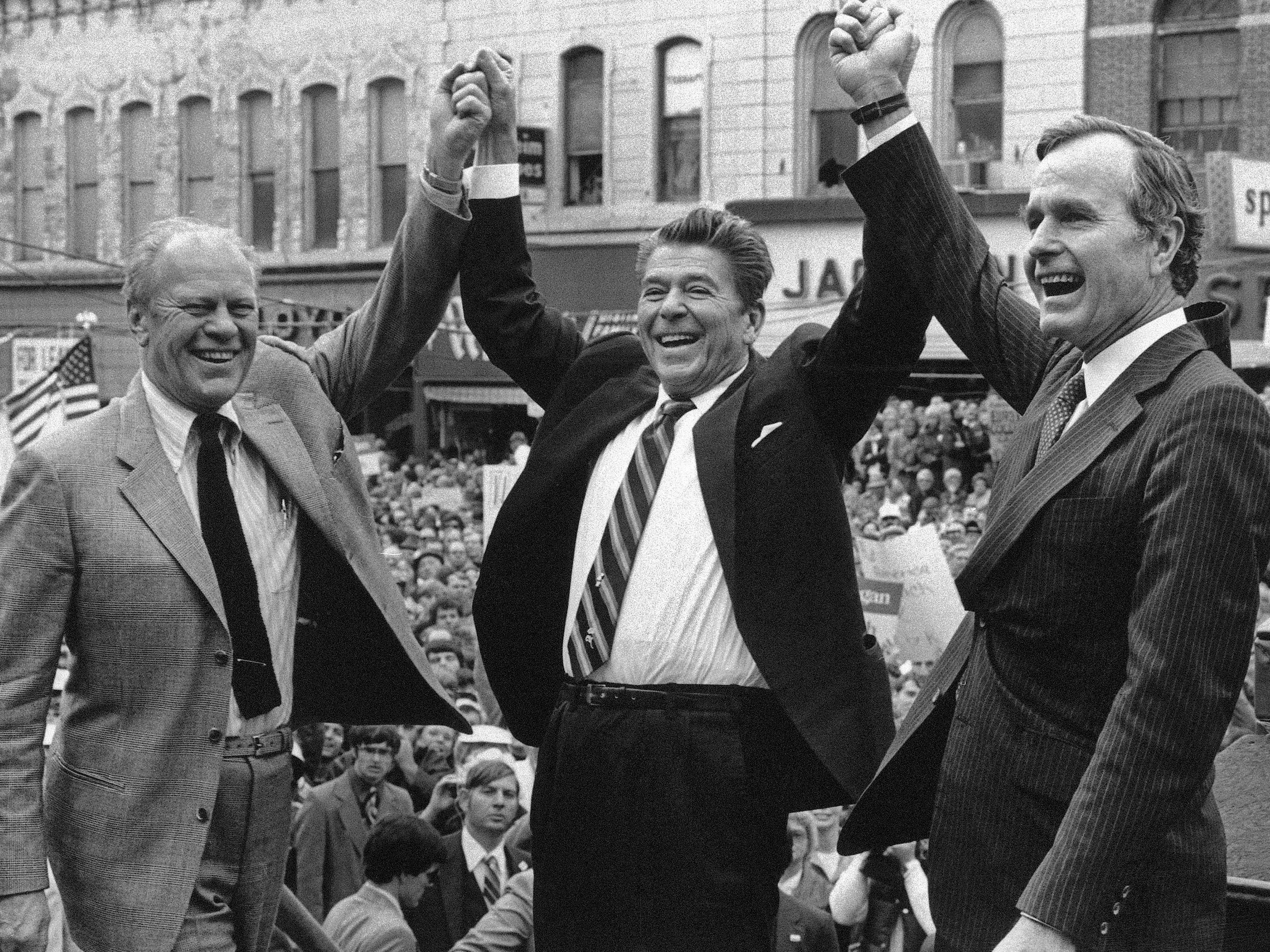 In this Nov. 3, 1980 photo, former President Gerald Ford lends his support to Republican presidential candidate Ronald Reagan and his running mate, George H.W. Bush in Peoria, Ill.