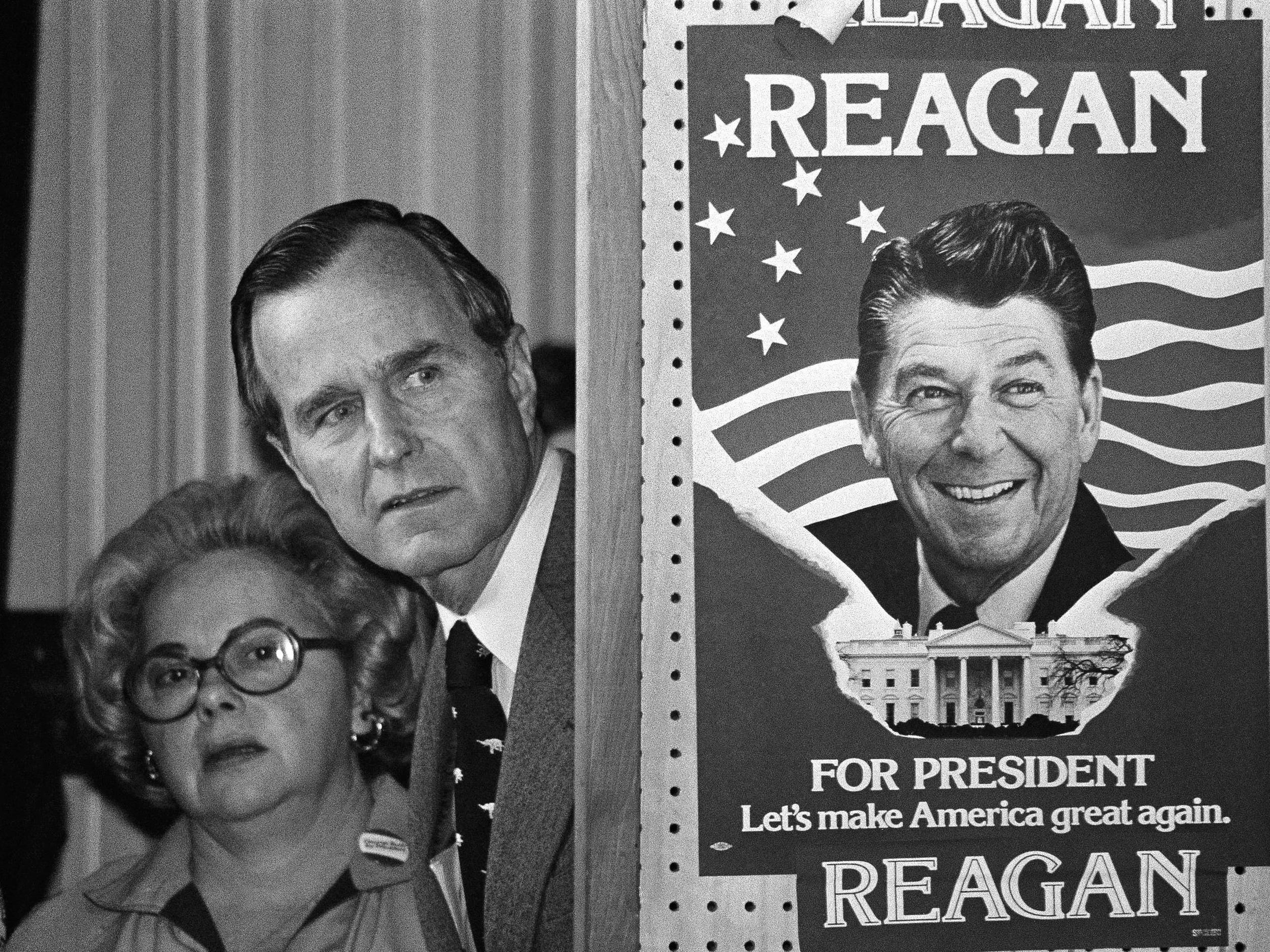 In this March 4, 1980 photo, George H.W. Bush and an unidentified woman peek around a partition with a poster of Ronald Reagan, one of his opponents for the Republican party presidential nomination, before he speaks in Columbia, S.C.