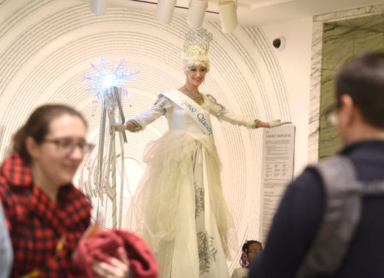 The Snow Queen poses for photographs in Prentis Court at the Detroit Institute of Art during Noel Night in Detroit on Saturday.