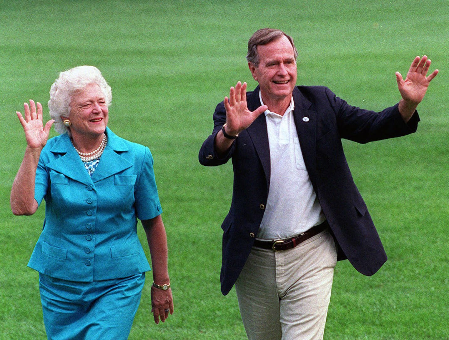 President George H.W. Bush and first lady Barbara Bush walk with their dog Millie across the South Lawn as they return to the White House on Aug. 24, 1992.