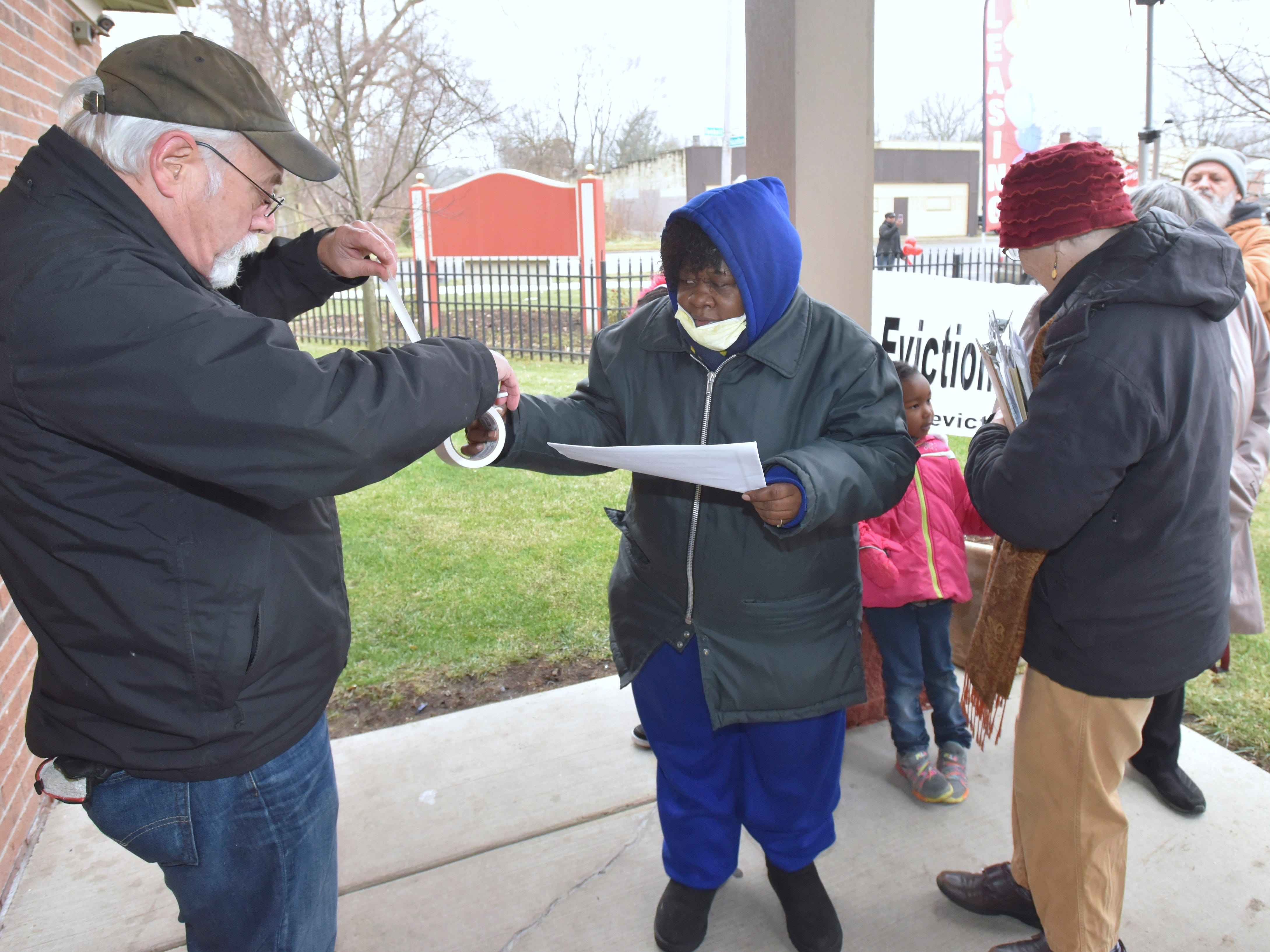 Supporter Steve Babson, left, and six-year Brightmoor Homes resident Helen Bryant, both of Detroit, prepare to post one of their eviction notices.