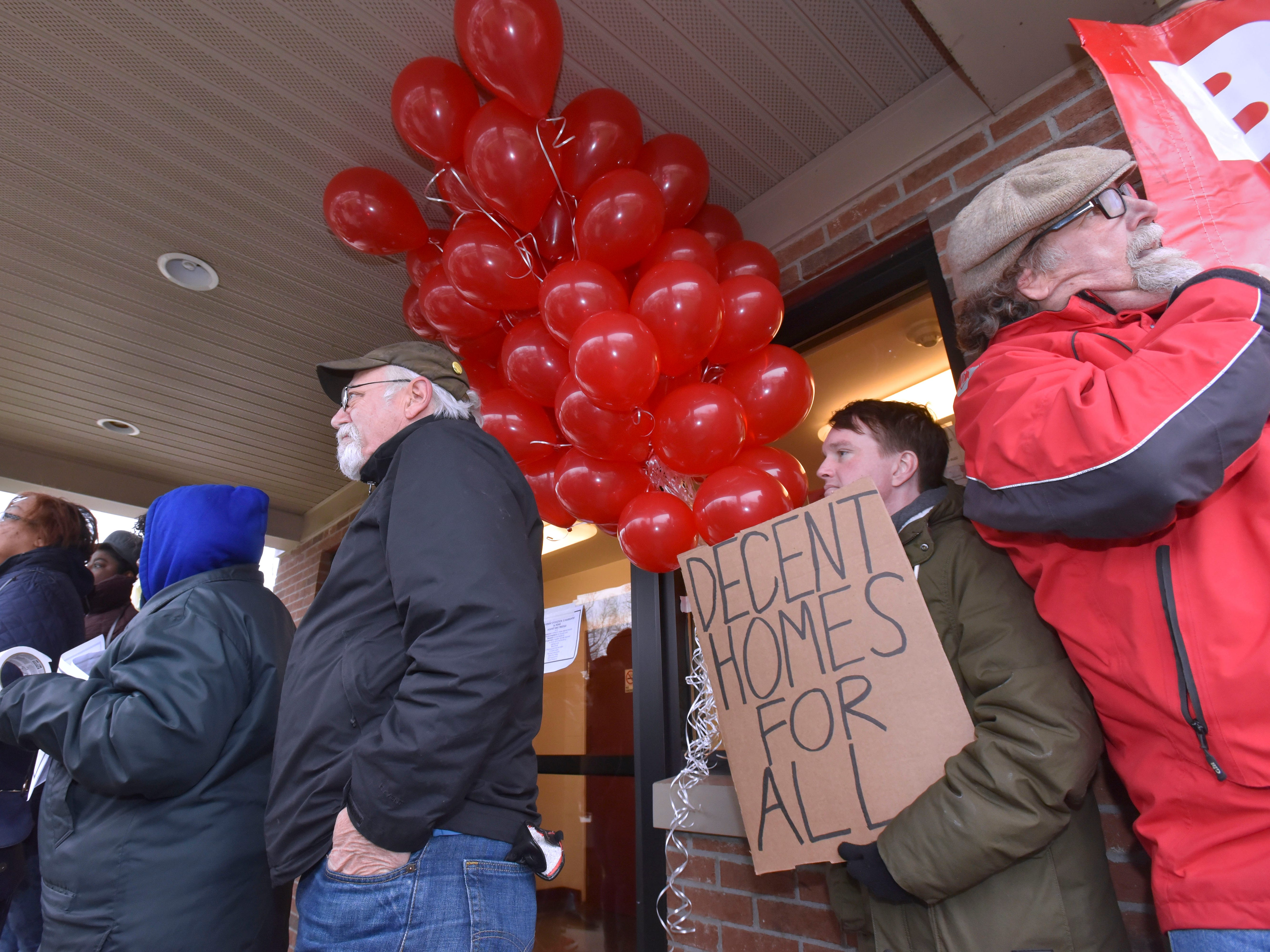 Supporter Joe McGuire, center, of Dearborn, holds a Decent Homes For All poster during the protest action.