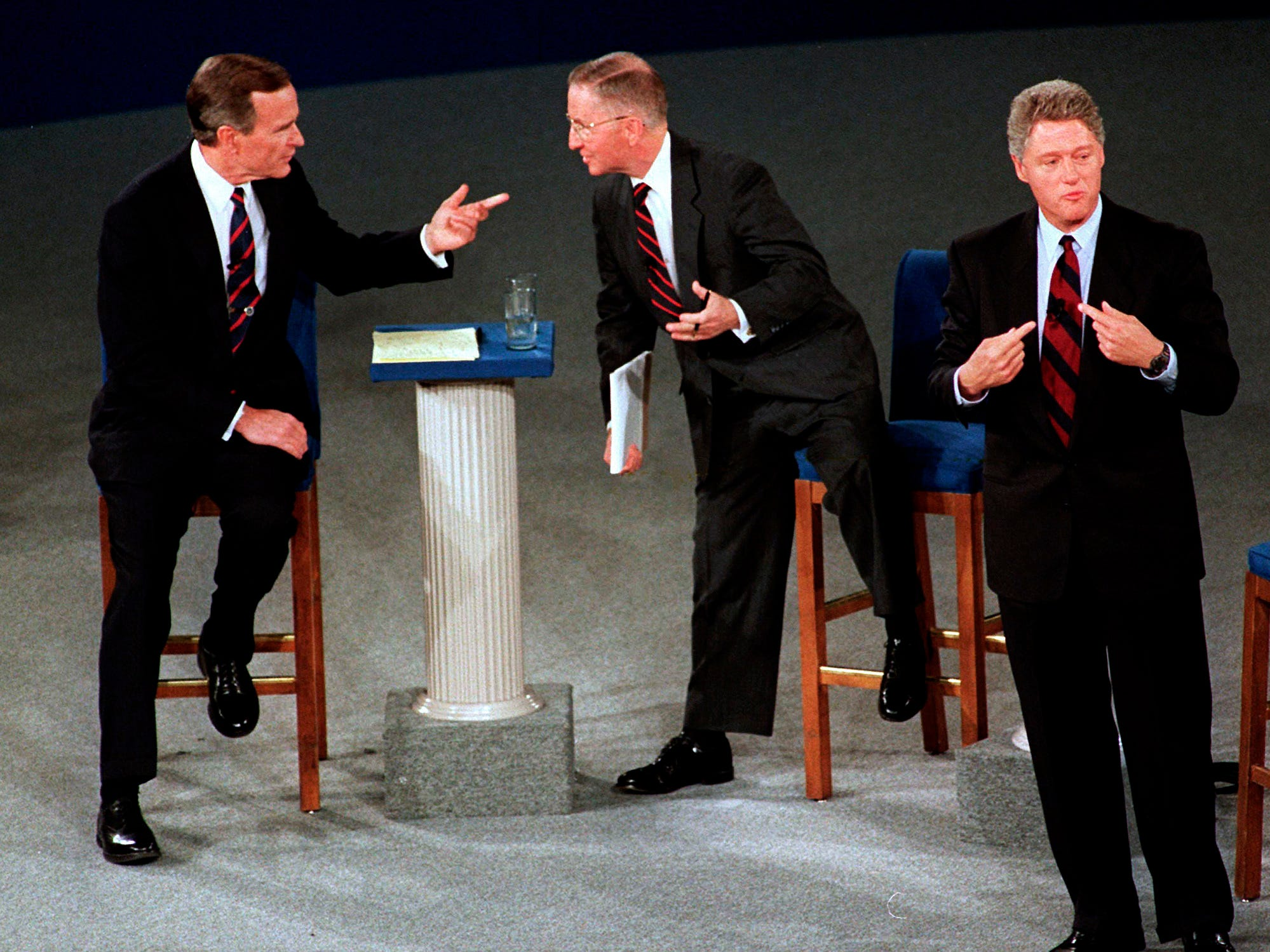 On Oct. 15, 1992, President George H.W. Bush, left, talks with independent candidate Ross Perot as Democratic candidate Bill Clinton stands aside at the end of their second presidential debate in Richmond, Va.
