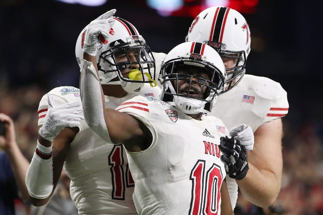 D.J. Brown of the Northern Illinois Huskies scores the game winning touchdown with Spencer Tears and Max Scharping while playing the Buffalo Bulls during the MAC Championship at Ford Field.