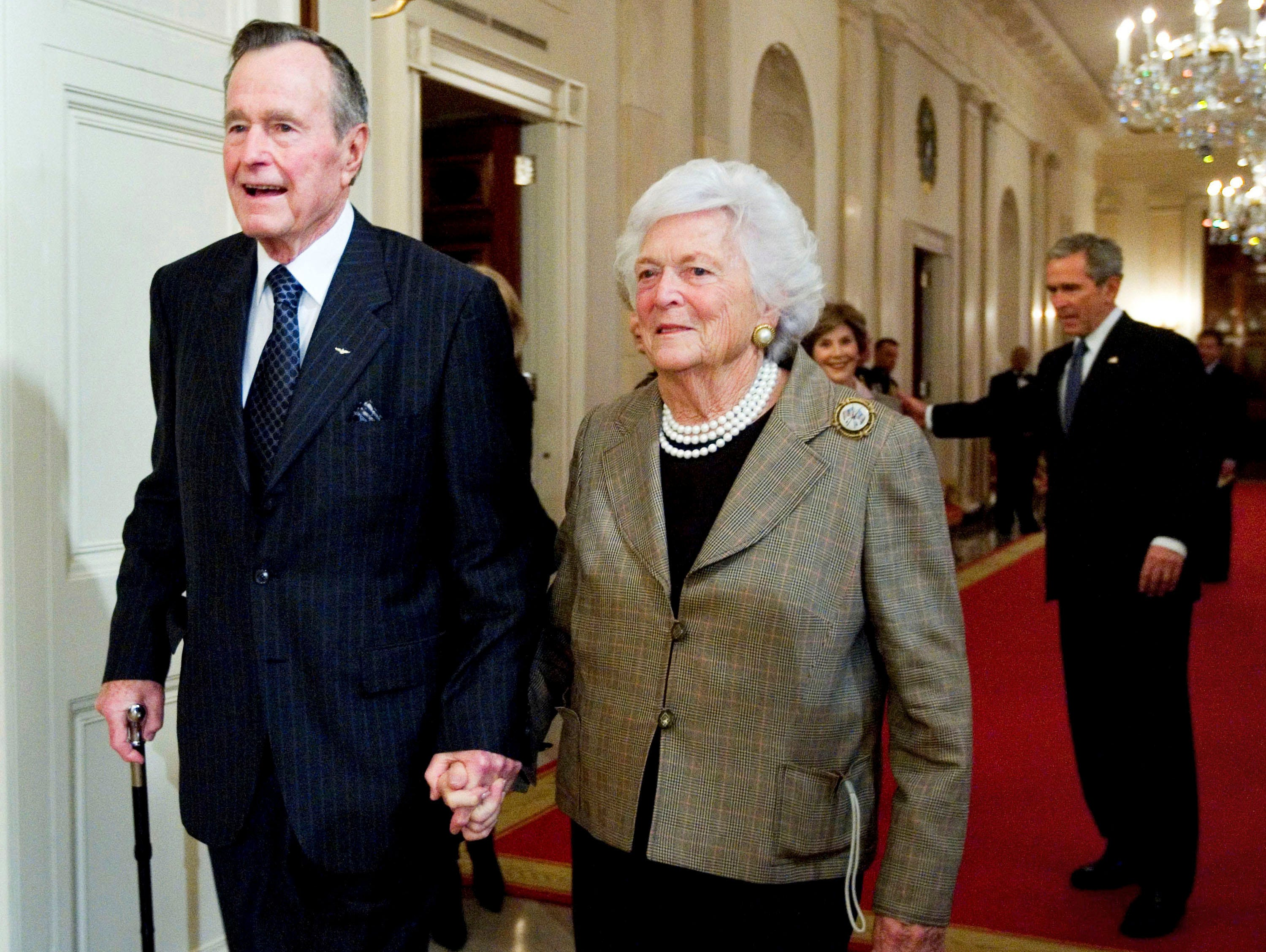 Former President George H. W. Bush, left, walks with his wife, former first lady Barbara Bush, followed by their son, President George W. Bush, and his wife first lady Laura Bush, to a Jan. 7, 2009 reception in honor of the Points of Light Institute, in the East Room at the White House in Washington.