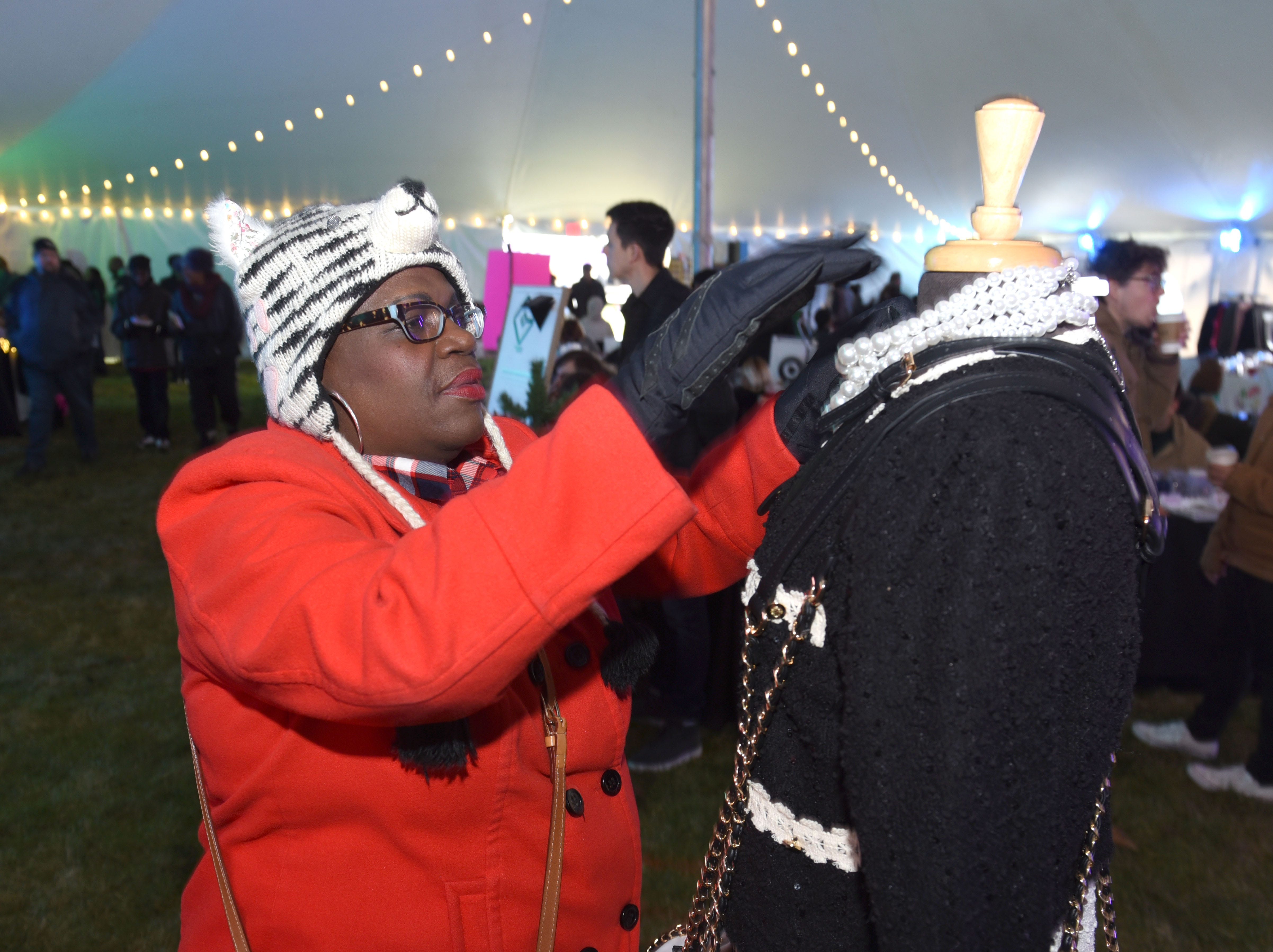 JeDonna Dinges, owner of Margaux & Max,  shows her collection of women's clothes, handbags, shoes, and accessories at the Winter Art and Retail Market during Noel Night events.