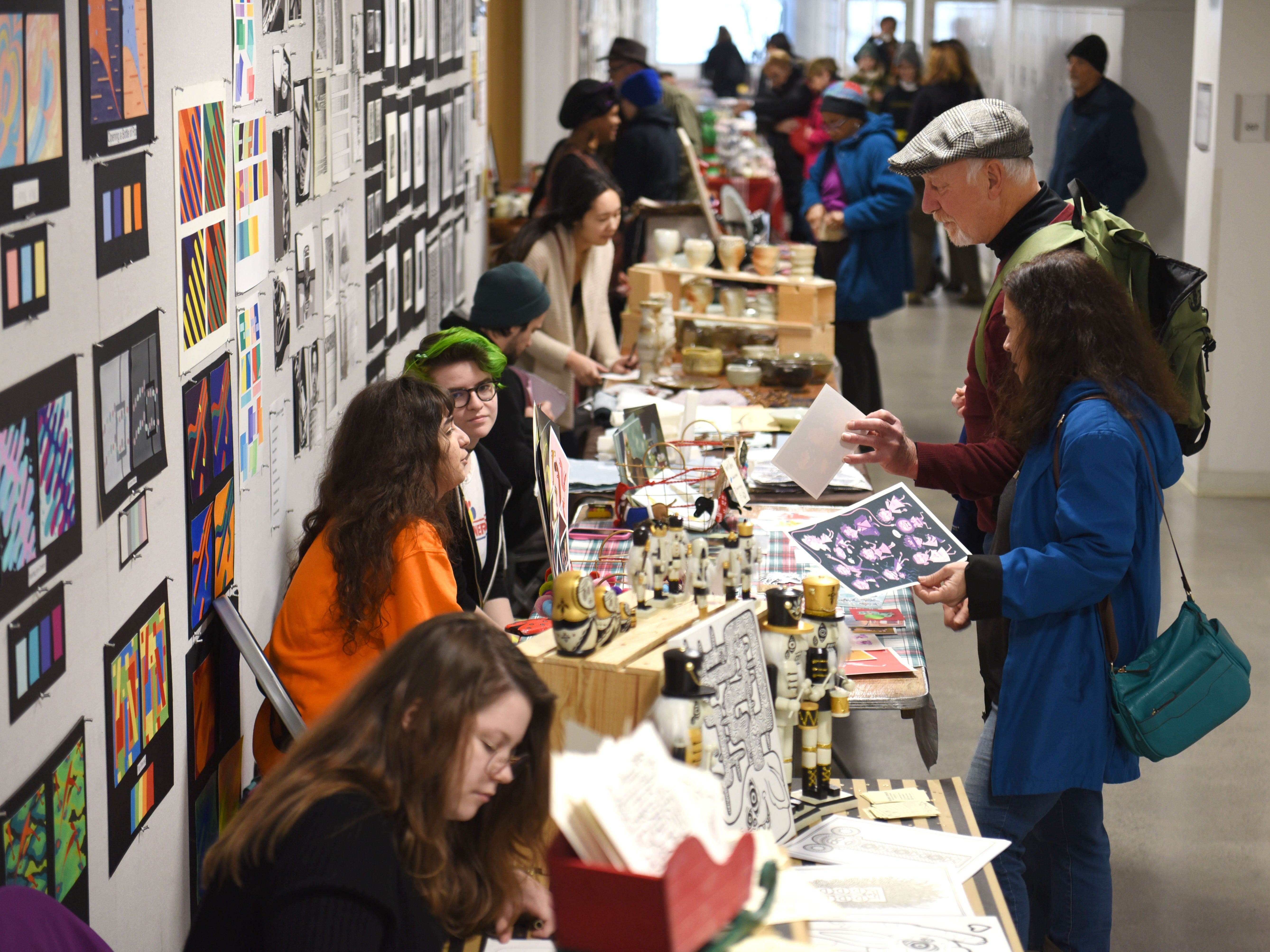 People look at artwork at the Annual Student Alumni Art Sale at the College of Creative Studies during Noel Night in Detroit on Saturday, December 1, 2018.