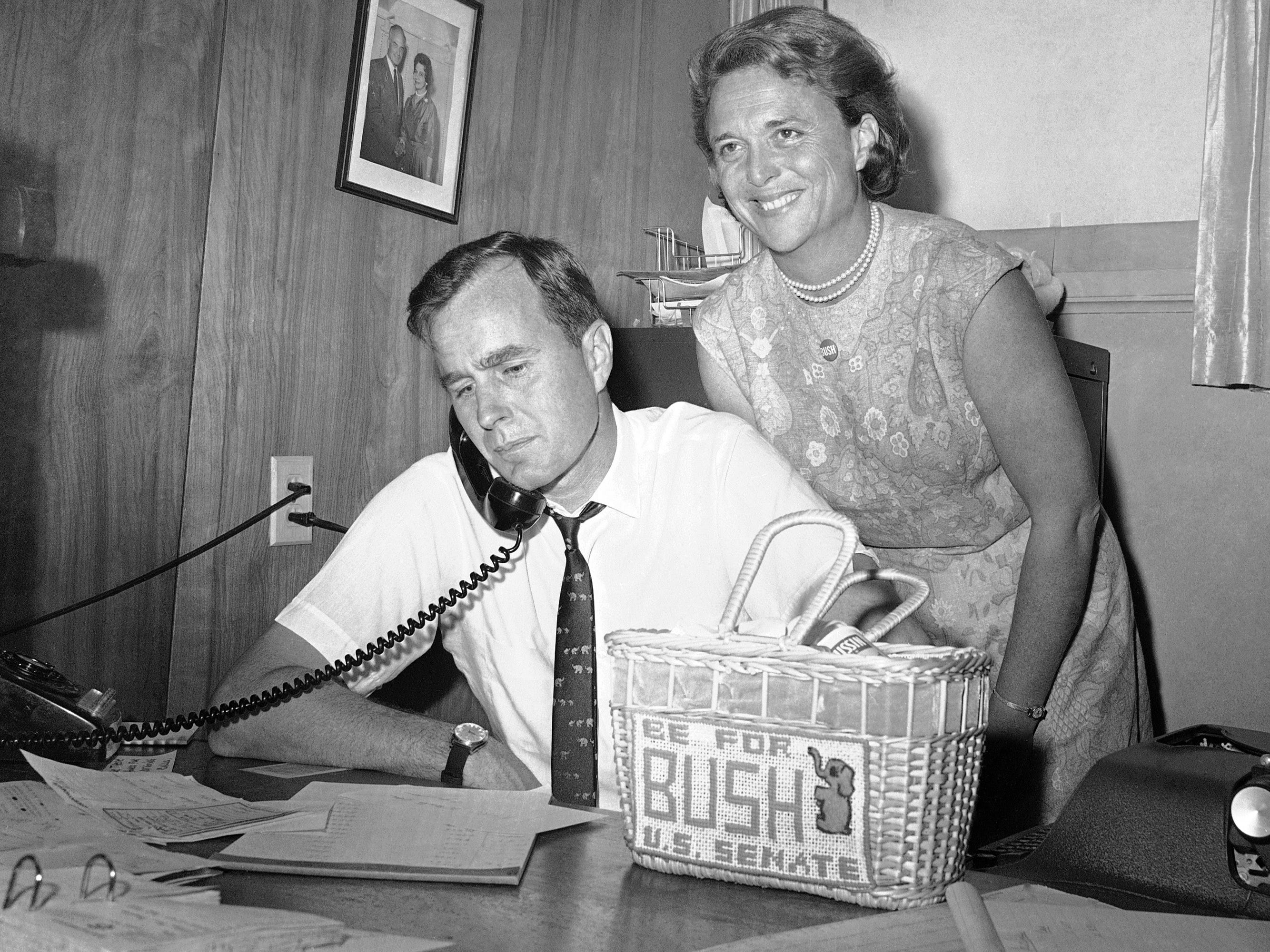 In this June 6, 1964 photo, George H.W. Bush, candidate for the Republican nomination for the U.S. Senate, gets ballot returns by phone at his headquarters in Houston, as his wife Barbara, smiles at the news.
