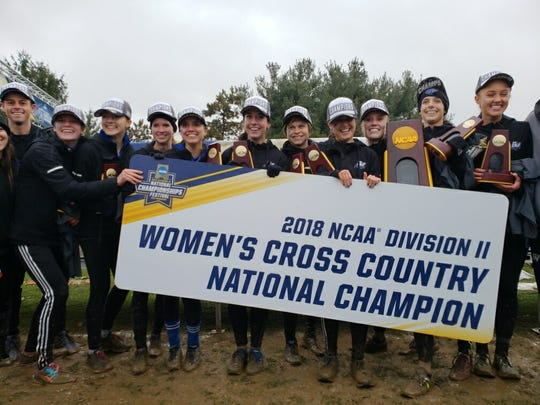 The Grand Valley State women's cross-country team celebrates Saturday.