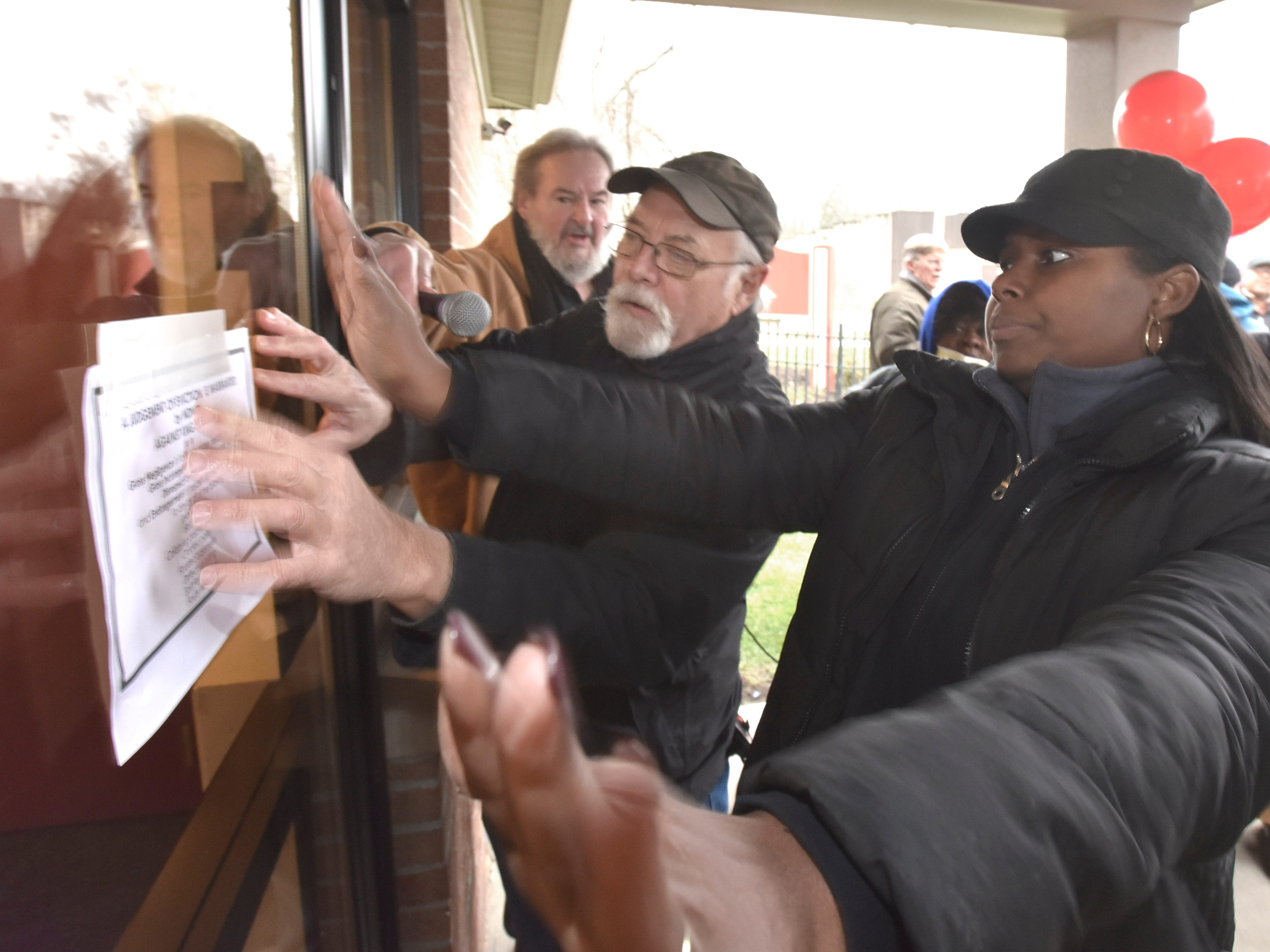 Supporter Steve Babson, left, and 19-year Brightmoor Homes resident and event organizer Soummer Crawford post one of their eviction notices on the front door of the KMG Prestige Management Company offices.