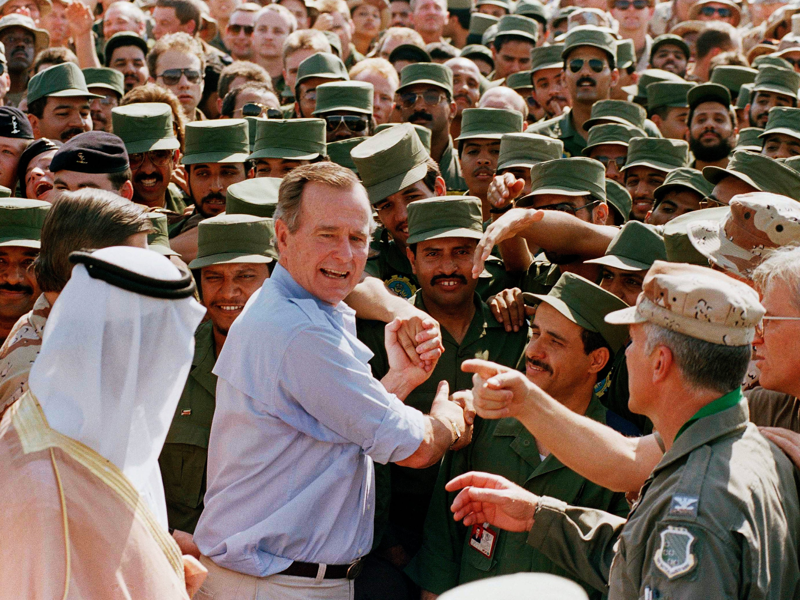 President George H.W. Bush is greeted by Saudi troops and others as he arrives in Dhahran, Saudi Arabia, on Nov. 22, 1990,  for a Thanksgiving visit. Bush died at the age of 94 on Friday, Nov. 30, 2018, about eight months after the death of his wife, Barbara Bush.