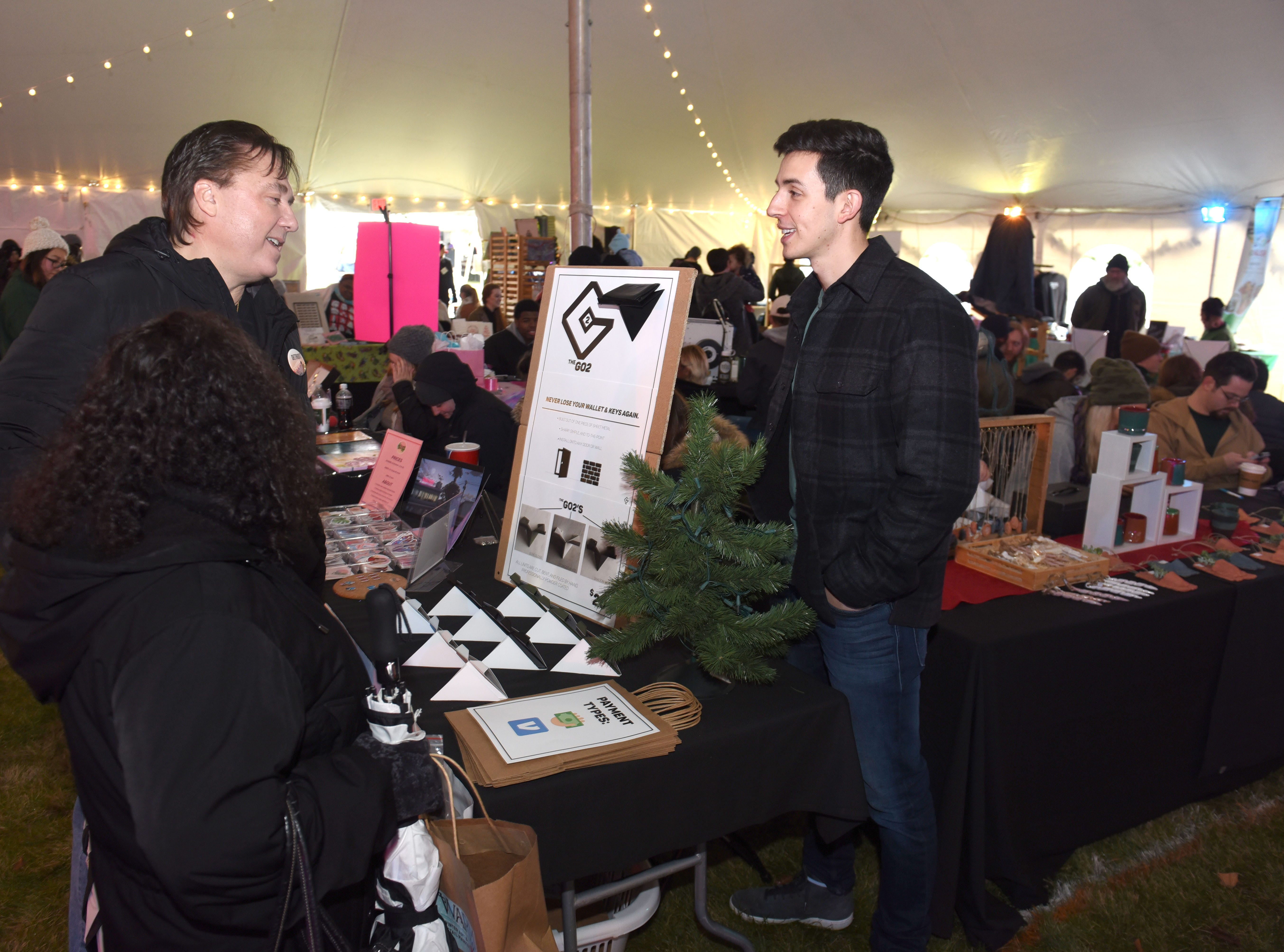 Wayne State University student Jacob Joye (right) speaks to customers at the Winter Art and Retail Market  about his GO2's invention during Noel Night.