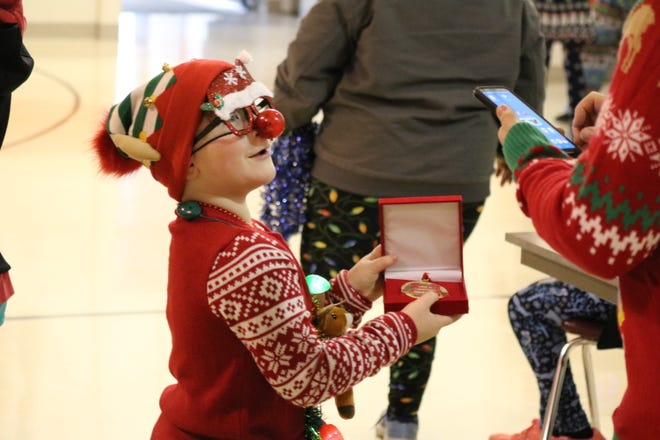 Case Gerwin, 6, of Gibsonburg, shows off his first place medal from the Ugly Christmas Sweater 5K Run and Walk, as his dad, Charlie, gets ready to take a picture.