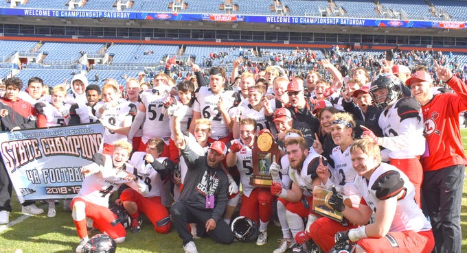 Loveland High School's football team celebrates with the trophy Saturday after winning the Class 4A state title.