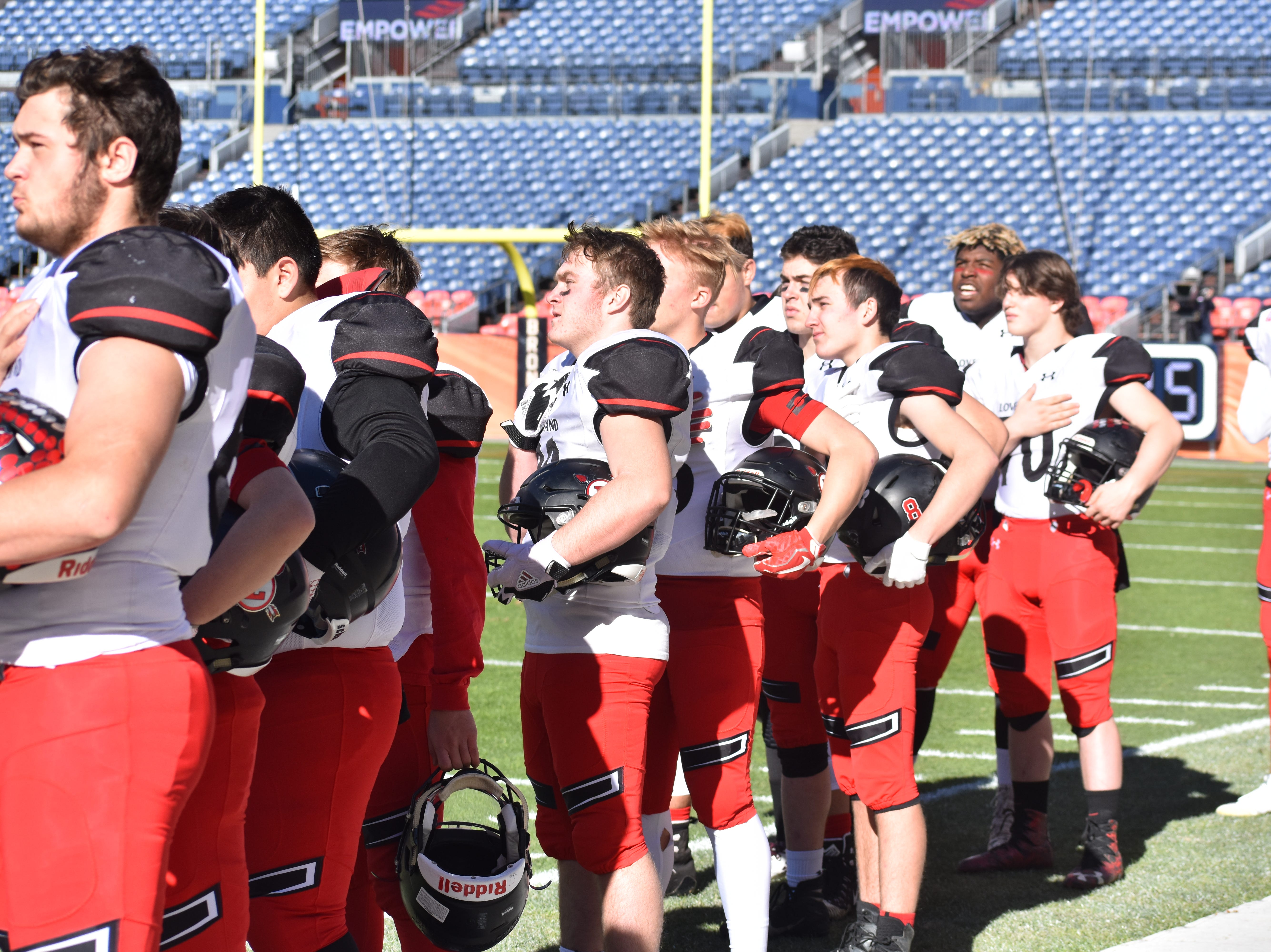 Loveland High football players look on during the singing of the national anthem prior to Saturday's Class 4A state championship game at Broncos Stadium at Mile High in Denver.