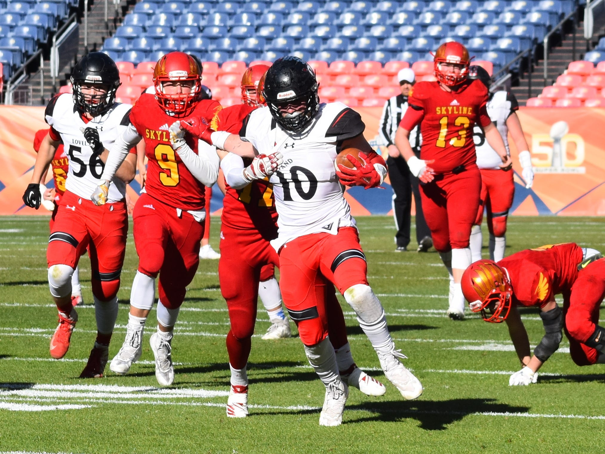 Loveland High School's Sean Boylan tries to break away from a Skyline defender during Saturday's Class 4A state championship football game in Denver.
