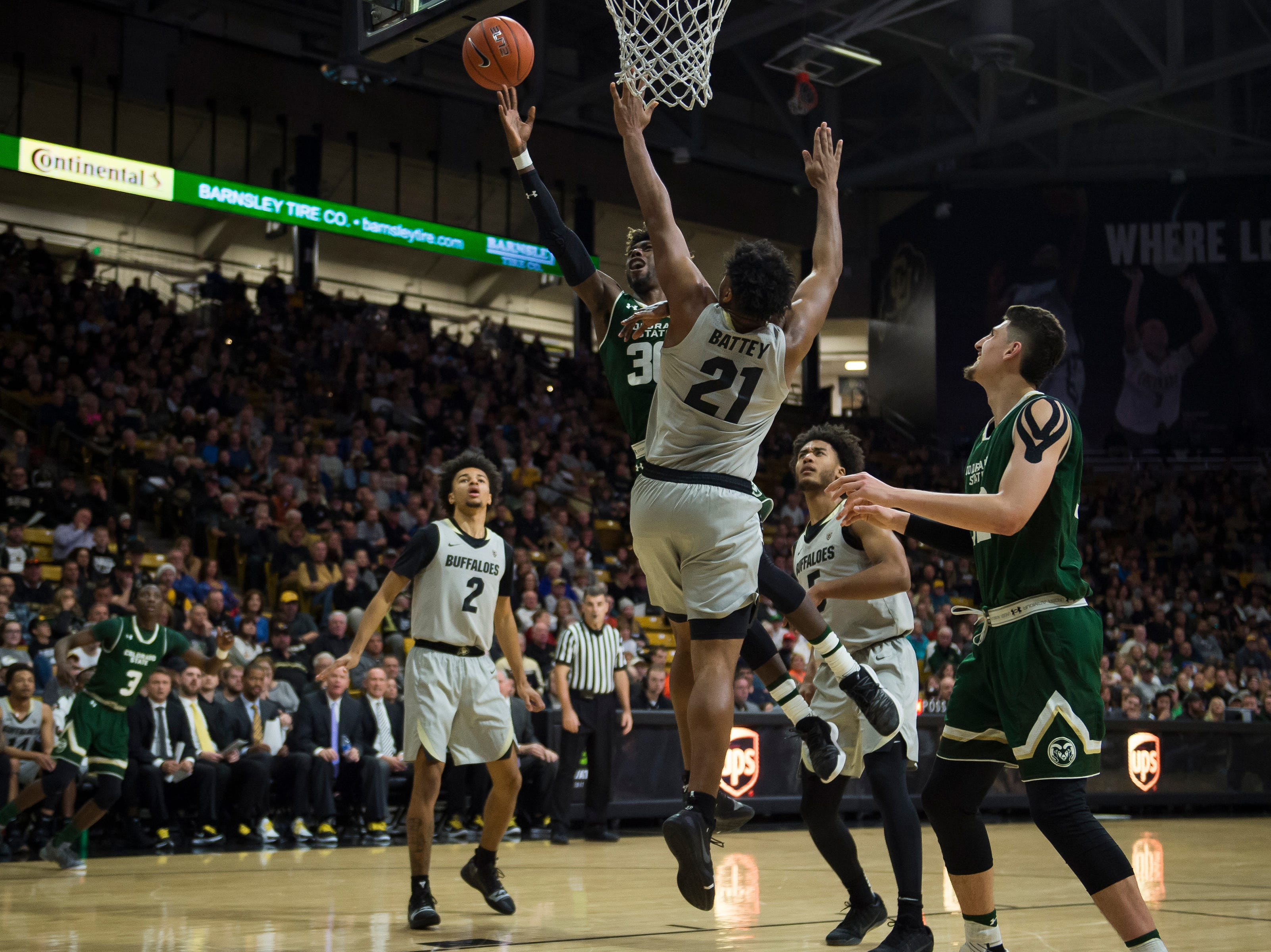 Colorado State University junior guard Kris Martin (30) gets a shot past University of Colorado freshman forward Evan Battey (21) on Saturday, Dec. 1, 2018, at the CU Event Center in Boulder, Colo.