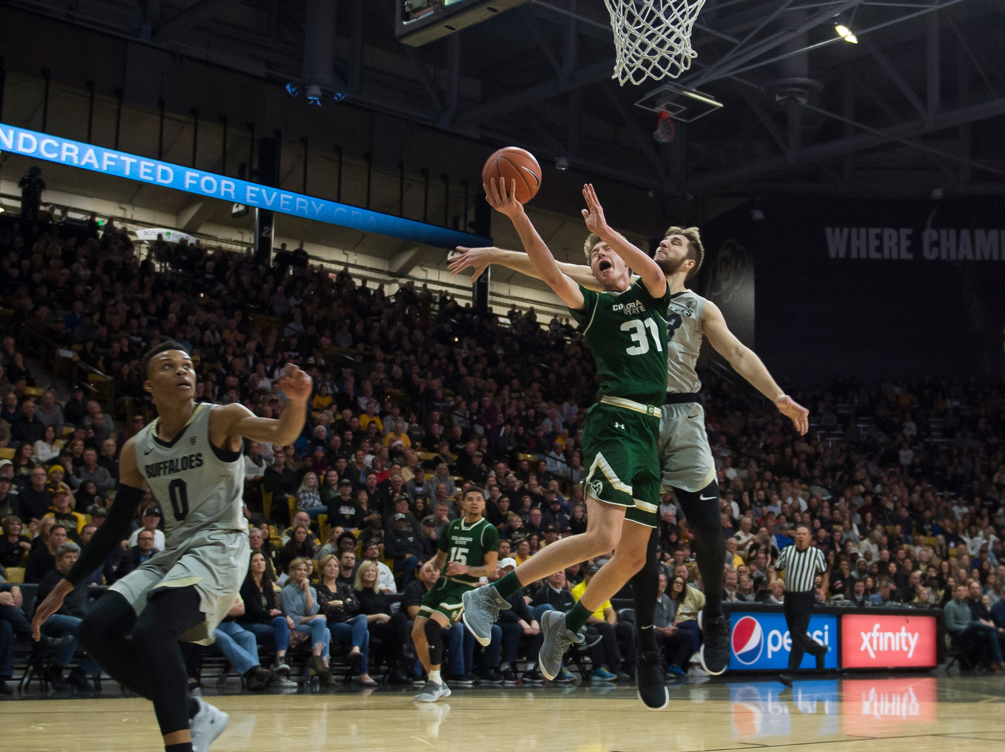 Colorado State University freshman forward Adam Thistlewood (31) gets a layup past University of Colorado junior forward Lucas Siewert (23) on Saturday, Dec. 1, 2018, at the CU Event Center in Boulder, Colo.