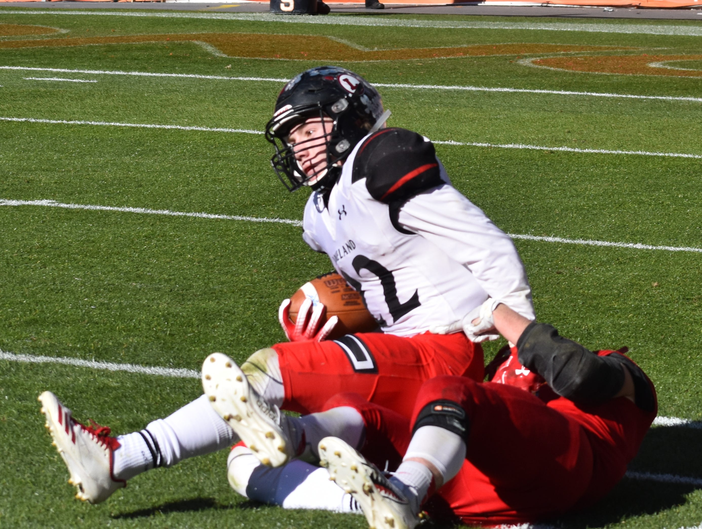 Loveland's Mason Adams is hauled down by a Skyline defender after making a catch for a 37-yard gain Saturday during the Class 4A state championship game in Denver.