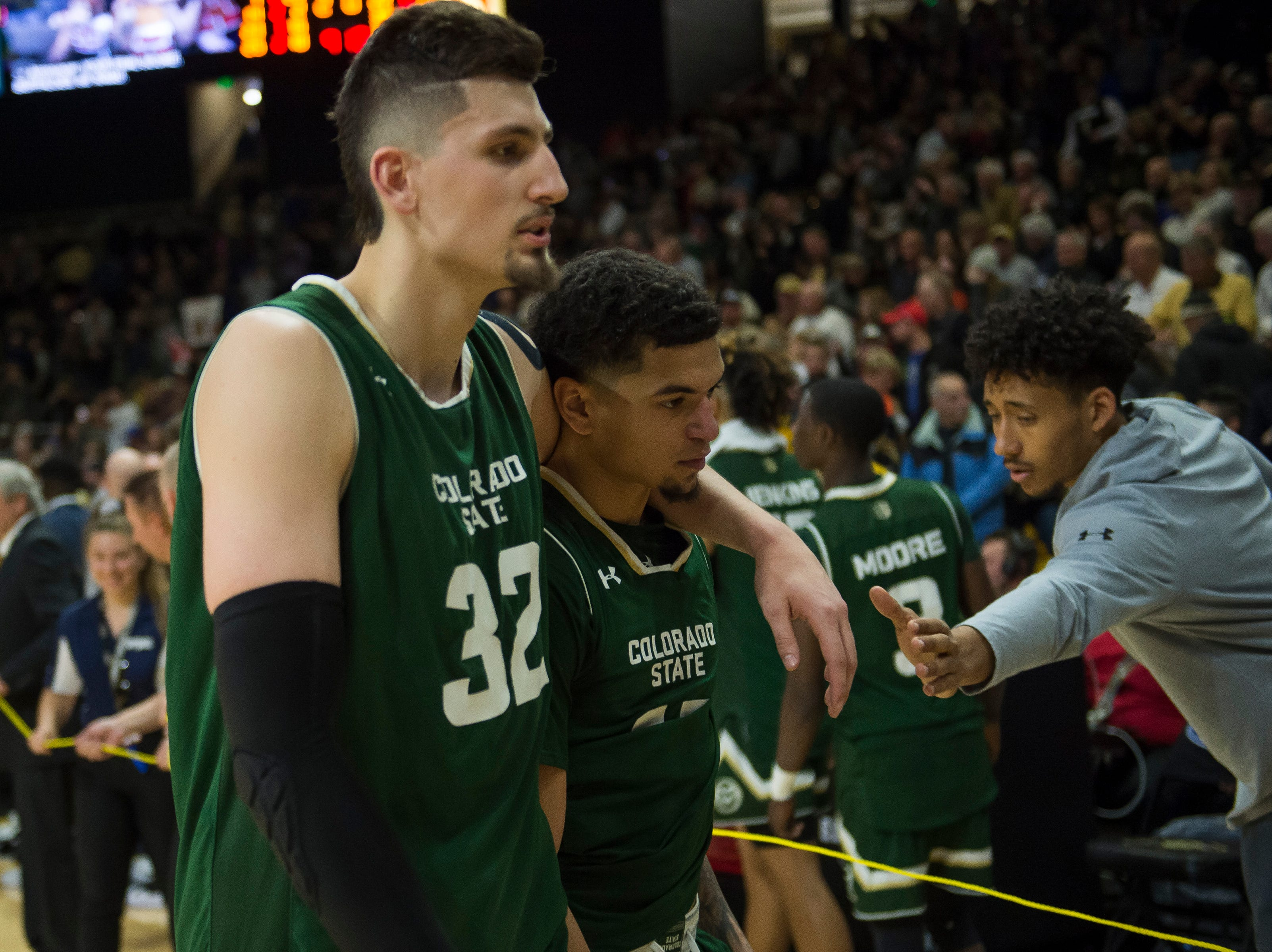 Colorado State University junior forward Nico Carvacho (32) comforts junior guard Anthony Masinton-Bonner (15) after losing a rivalry game against the University of Colorado on Saturday, Dec. 1, 2018, at the CU Event Center in Boulder, Colo.