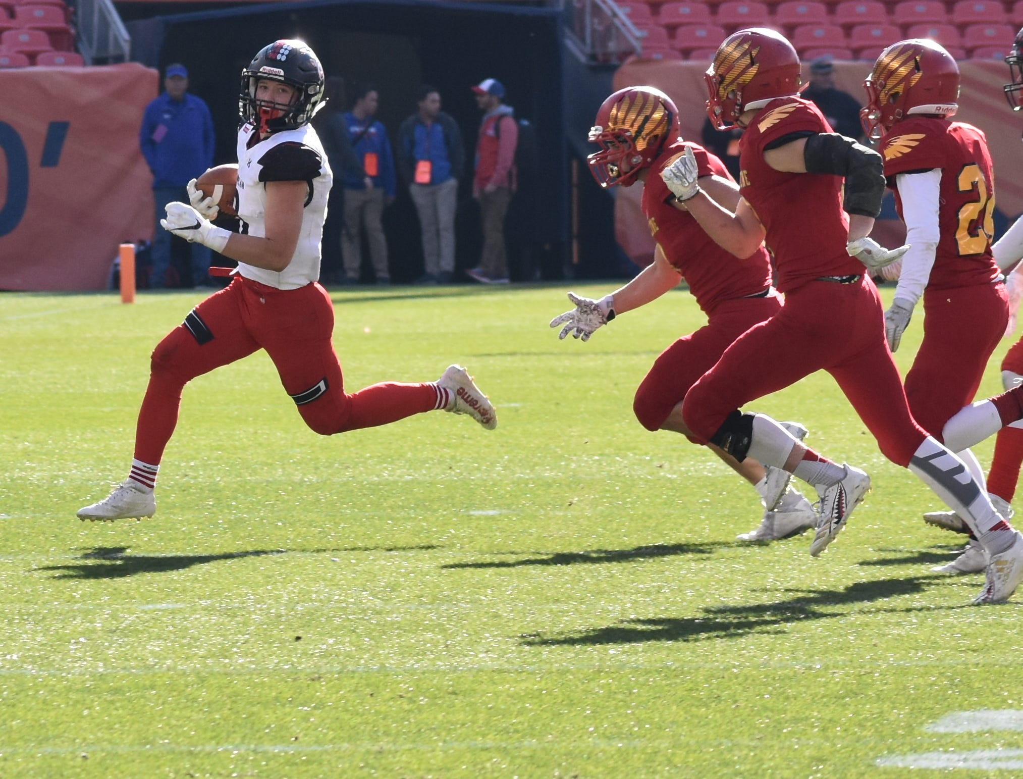 Loveland High School's Zach Weinmaster turns the corner while outrunning Skyline defenders during Saturday's Class 4A state championship game in Denver.